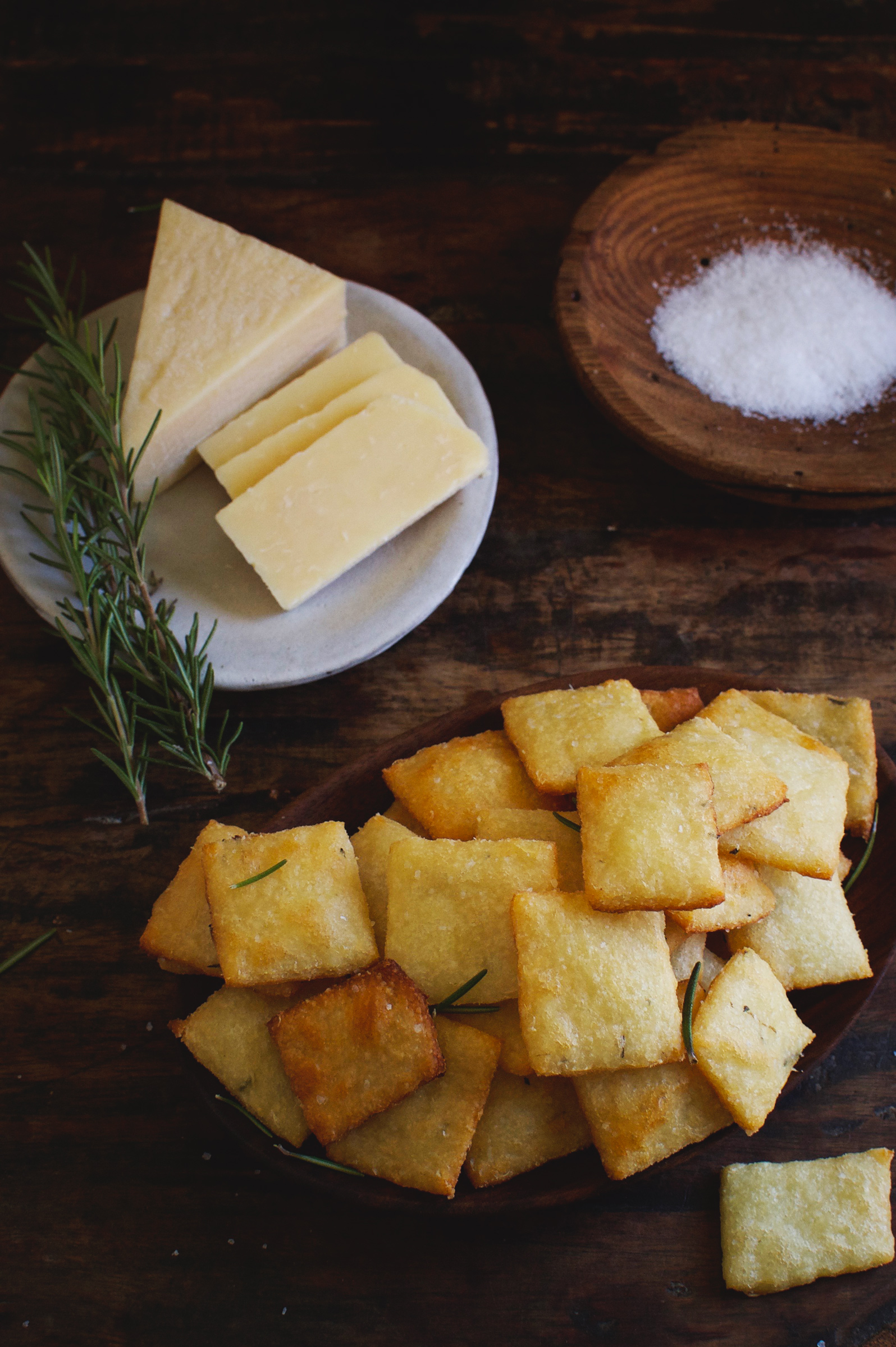 Low-Carb Rosemary Parmesan Crackers shown with rosemary, salt, and cheese.