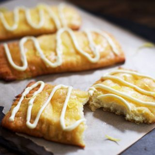 Close up photo of lemon danish pastries with one sliced in half.