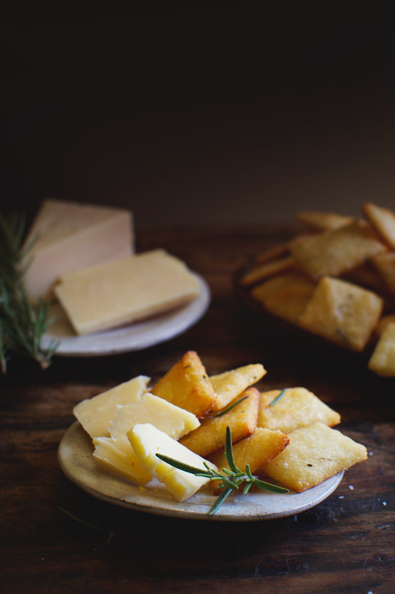 Low-Carb Rosemary Parmesan Crackers on a plate with cheese.