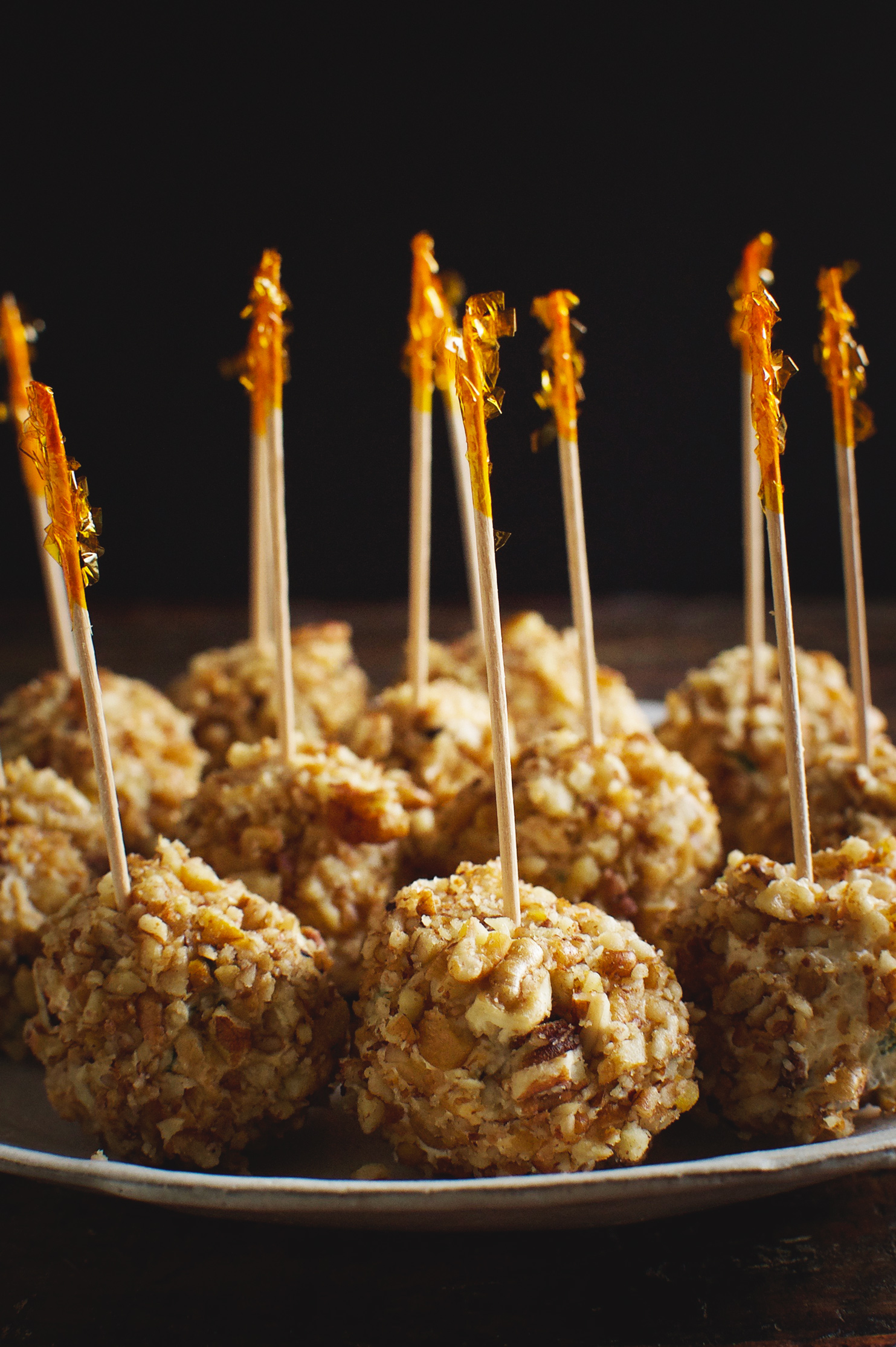 Low-Carb Mini Bacon Chive Cheeseballs on a plate with party picks in each one.
