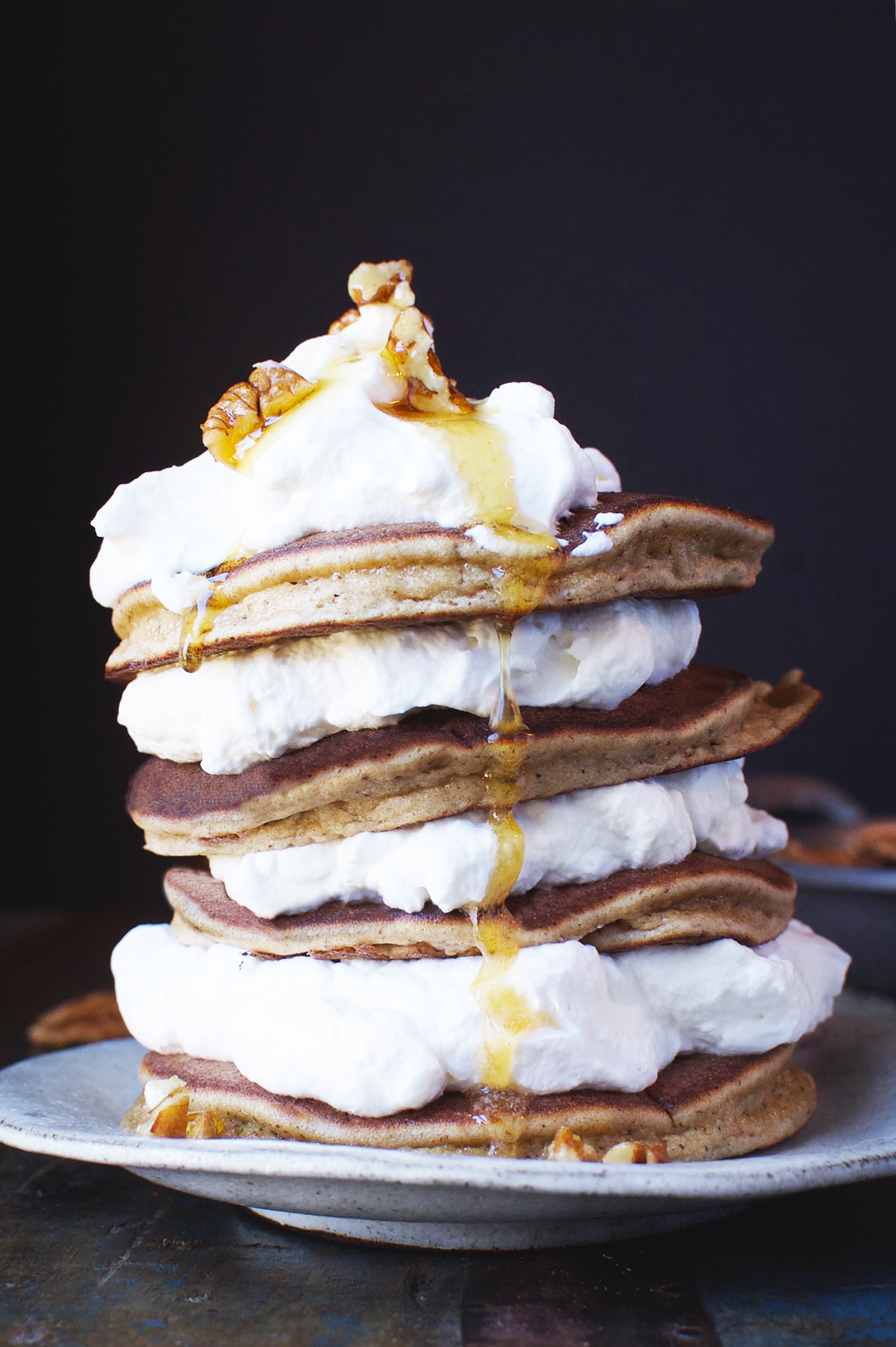 Low-Carb Banana Nut Pancakes stacked with whipped cream between, and syrup running over the top and down the sides.