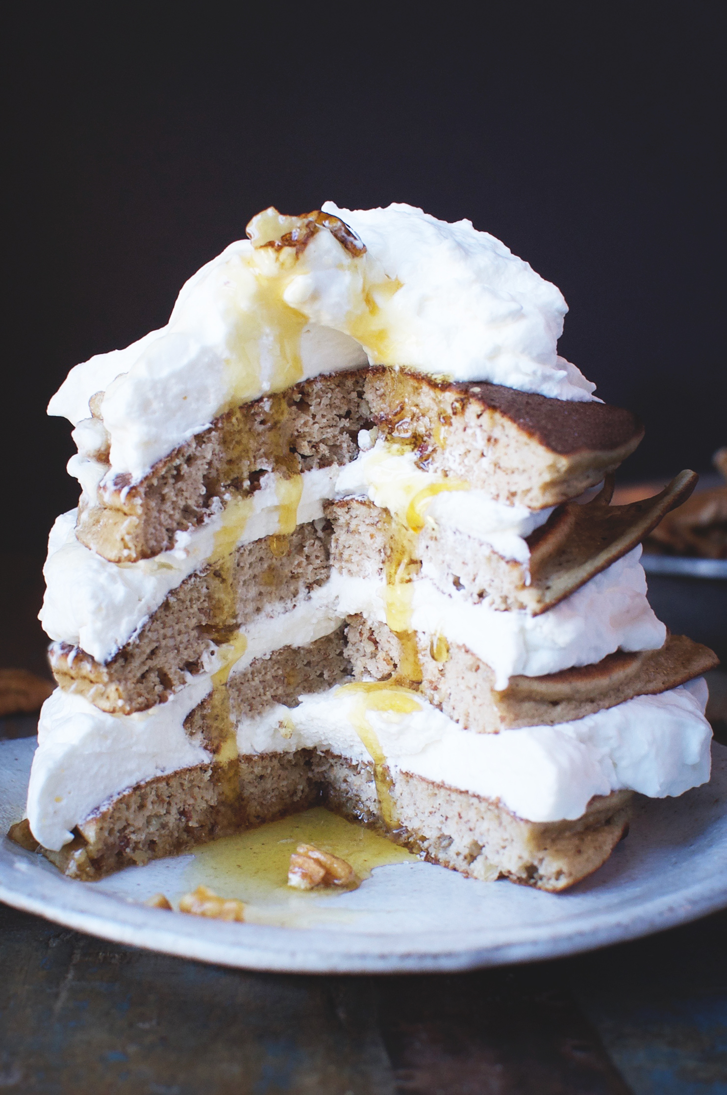 Low-Carb Banana Nut Pancakes stacked with whipped cream between and a piece cut out.