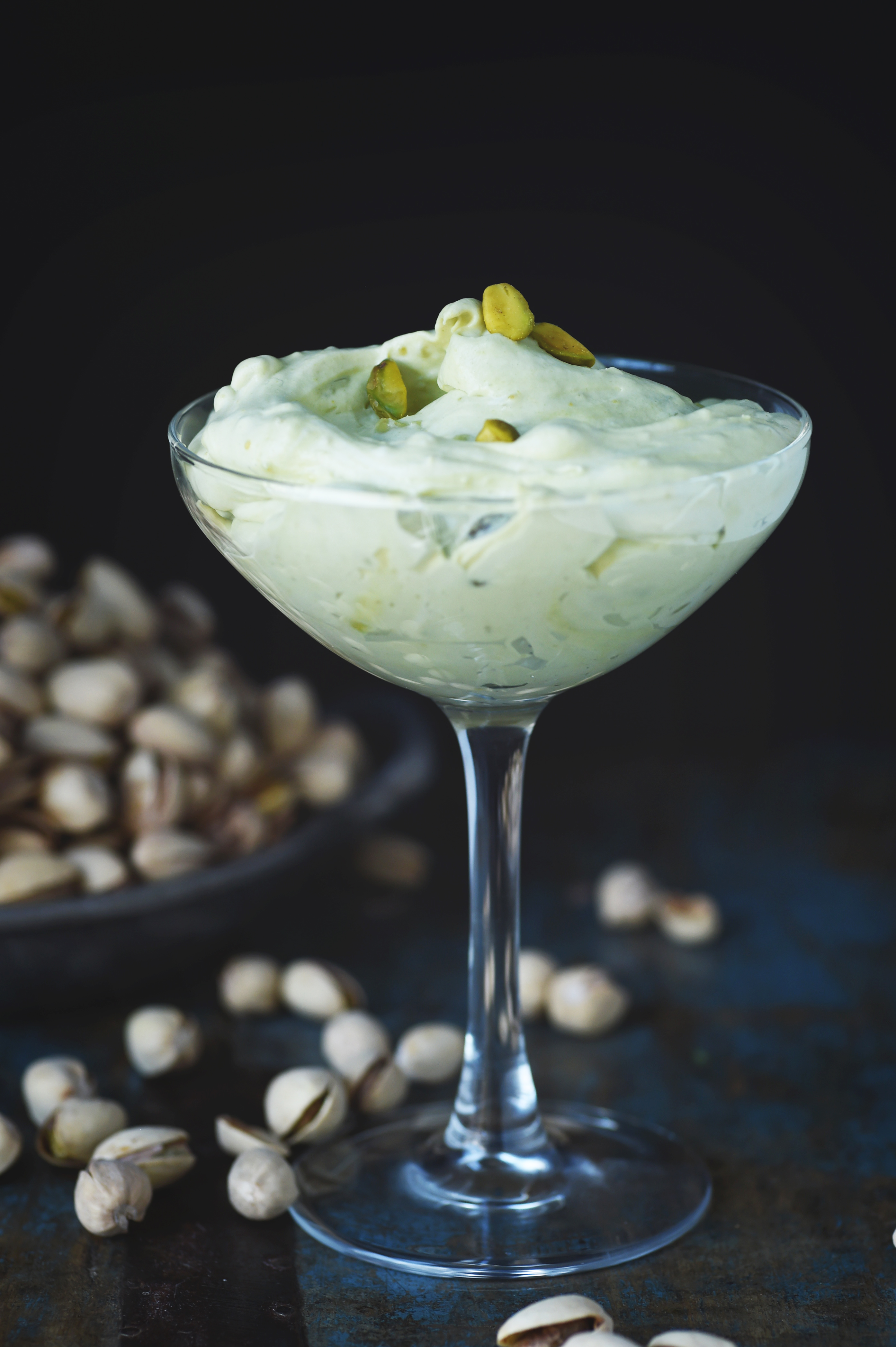 Low-Carb Pistachio Mousse Recipe served in a champagne glass with pistachios in the background.