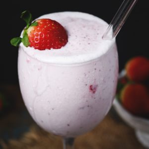 Low-Carb Strawberry Smoothie in a glass garnished with a strawberry.