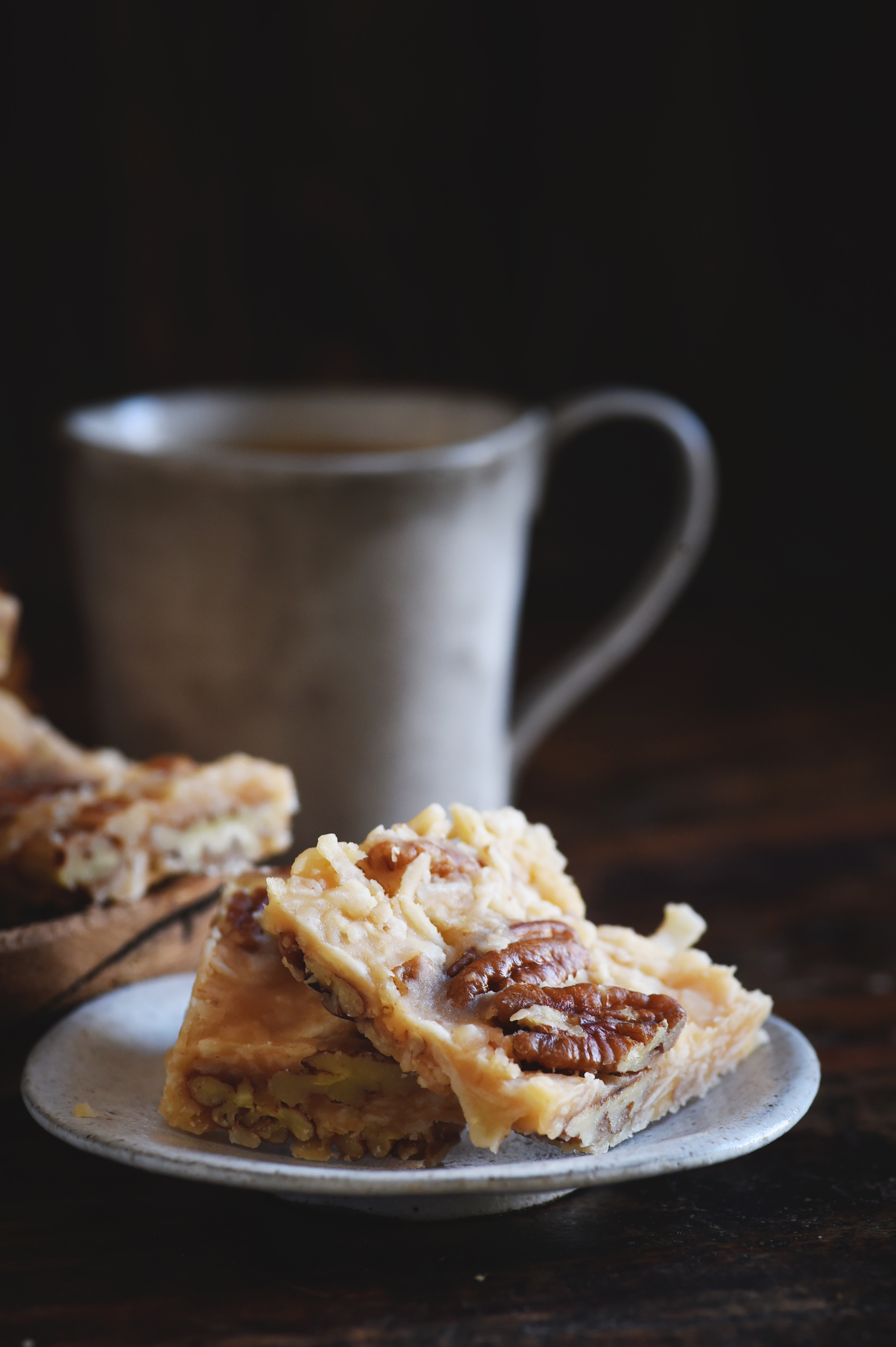 Low-Carb Coconut Pecan Snack Bar Recipe served on a plate with a cup of coffee.