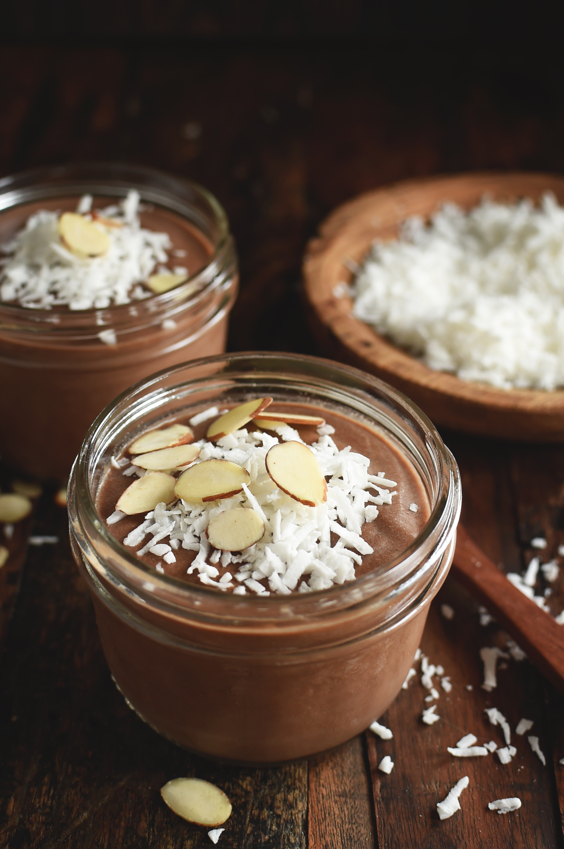 Chocolate Almond Avocado Pudding in a jar with flaked coconut in the background.