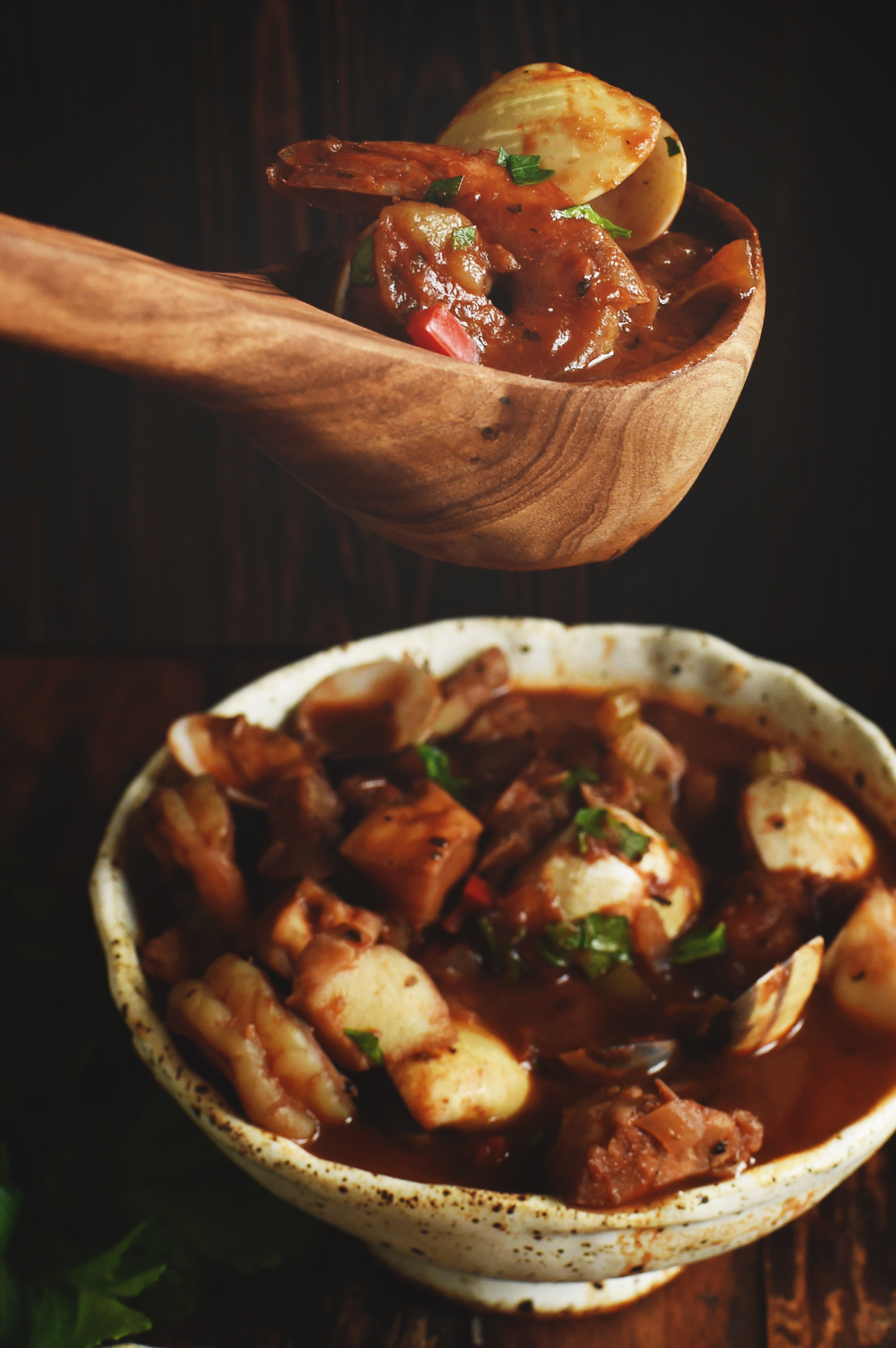 Cioppino Seafood Stew being spooned into a bowl.