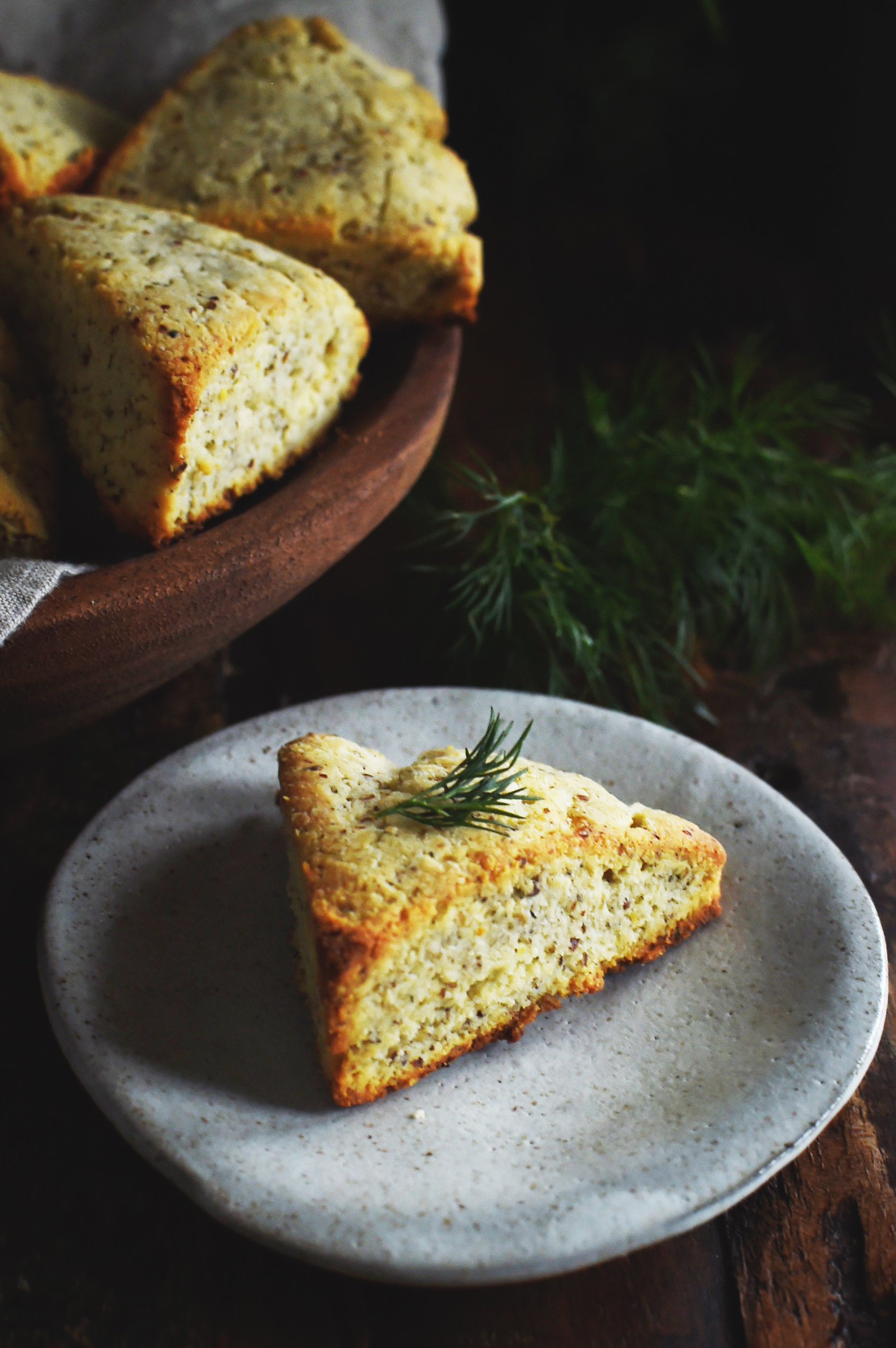 Low-Carb Onion Dill Savory Scones-a whole scone on a bread plate.