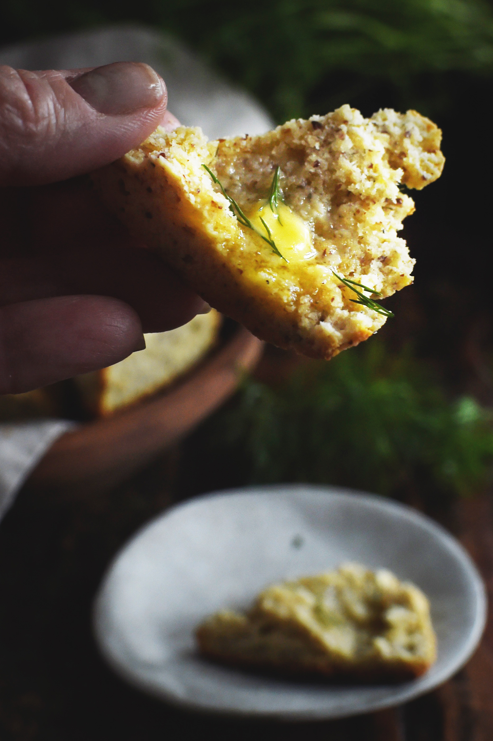 Low-Carb Onion Dill Savory Scones -holding a buttered half.