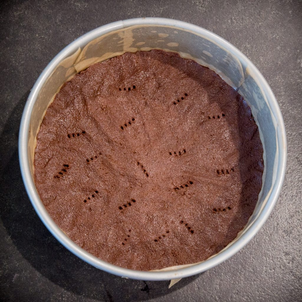 Process photo of unbaked pie crust in cake pan.