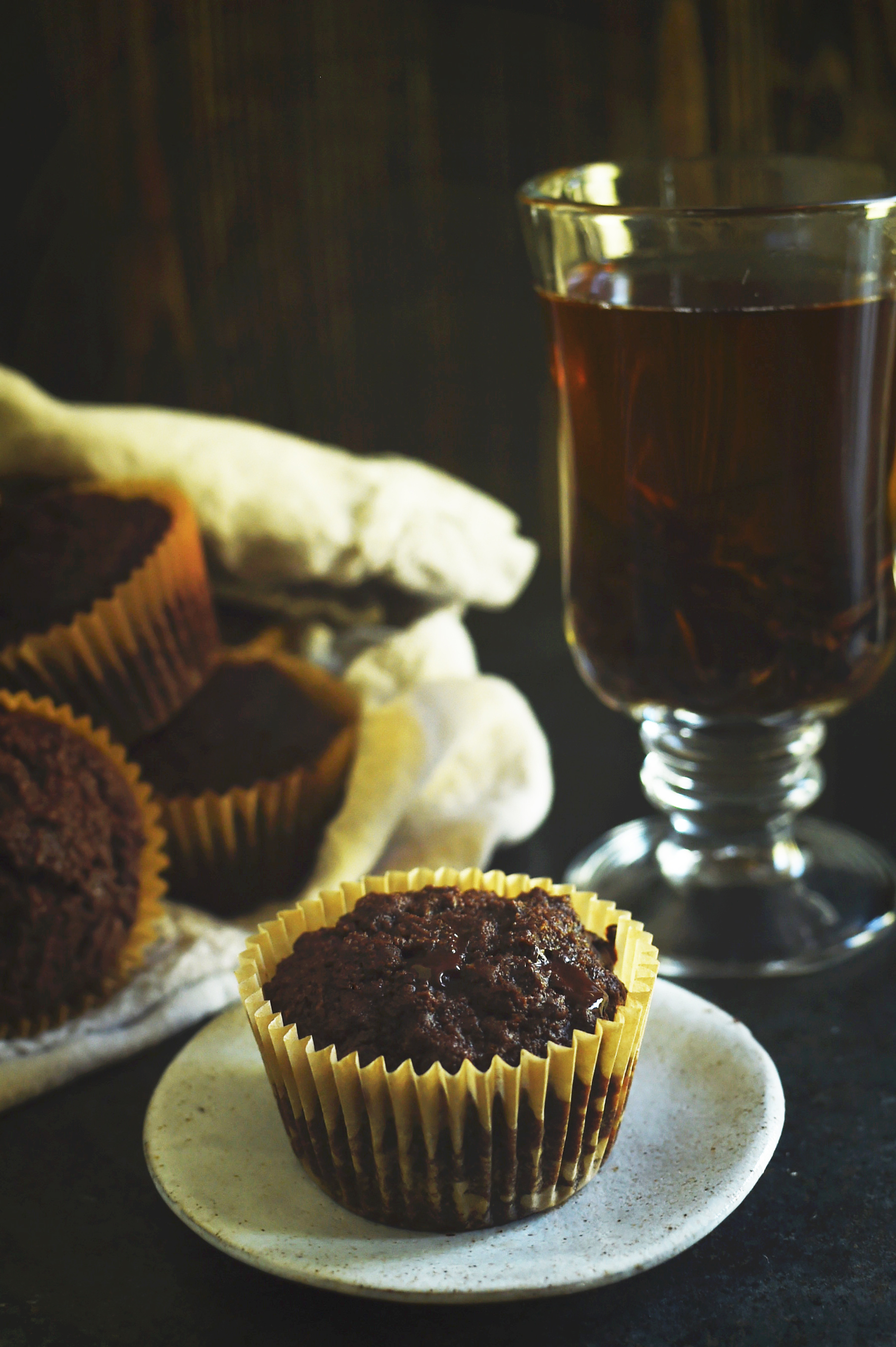 Low-Carb Double Chocolate Muffins Recipe-One muffin on a serving plate with tea behind.
