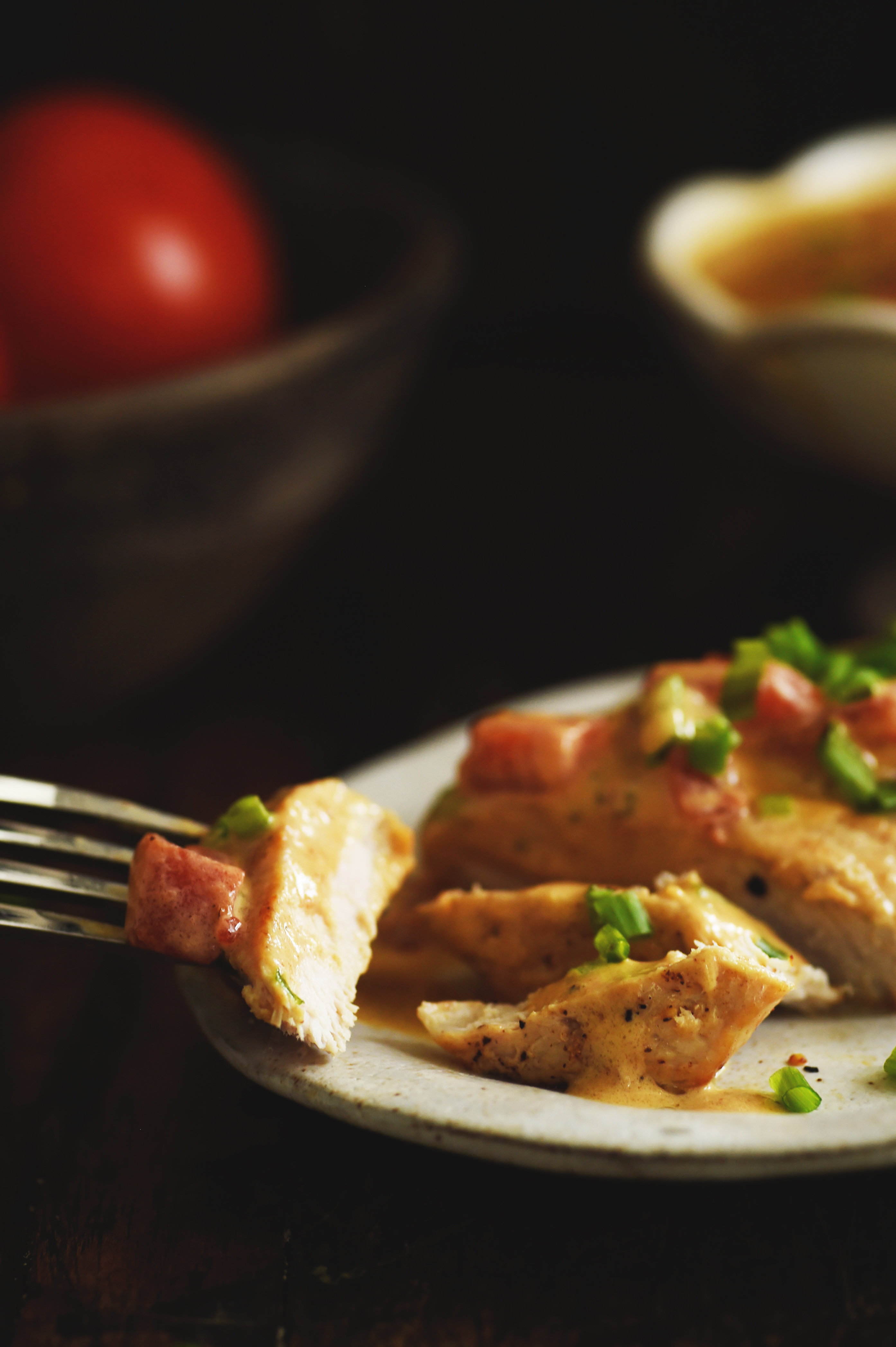 Boneless Pork Chops with Tomato Cream Sauce-A piece cut with a chunk on a fork.