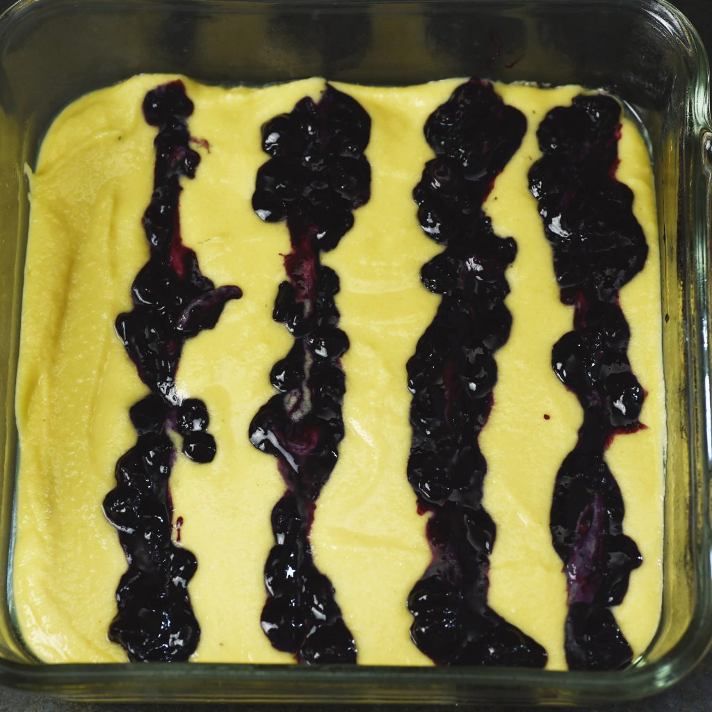 Low-Carb Blueberry Almond Flour Coffee Cake-Batter in pan with blueberries added in stripes.