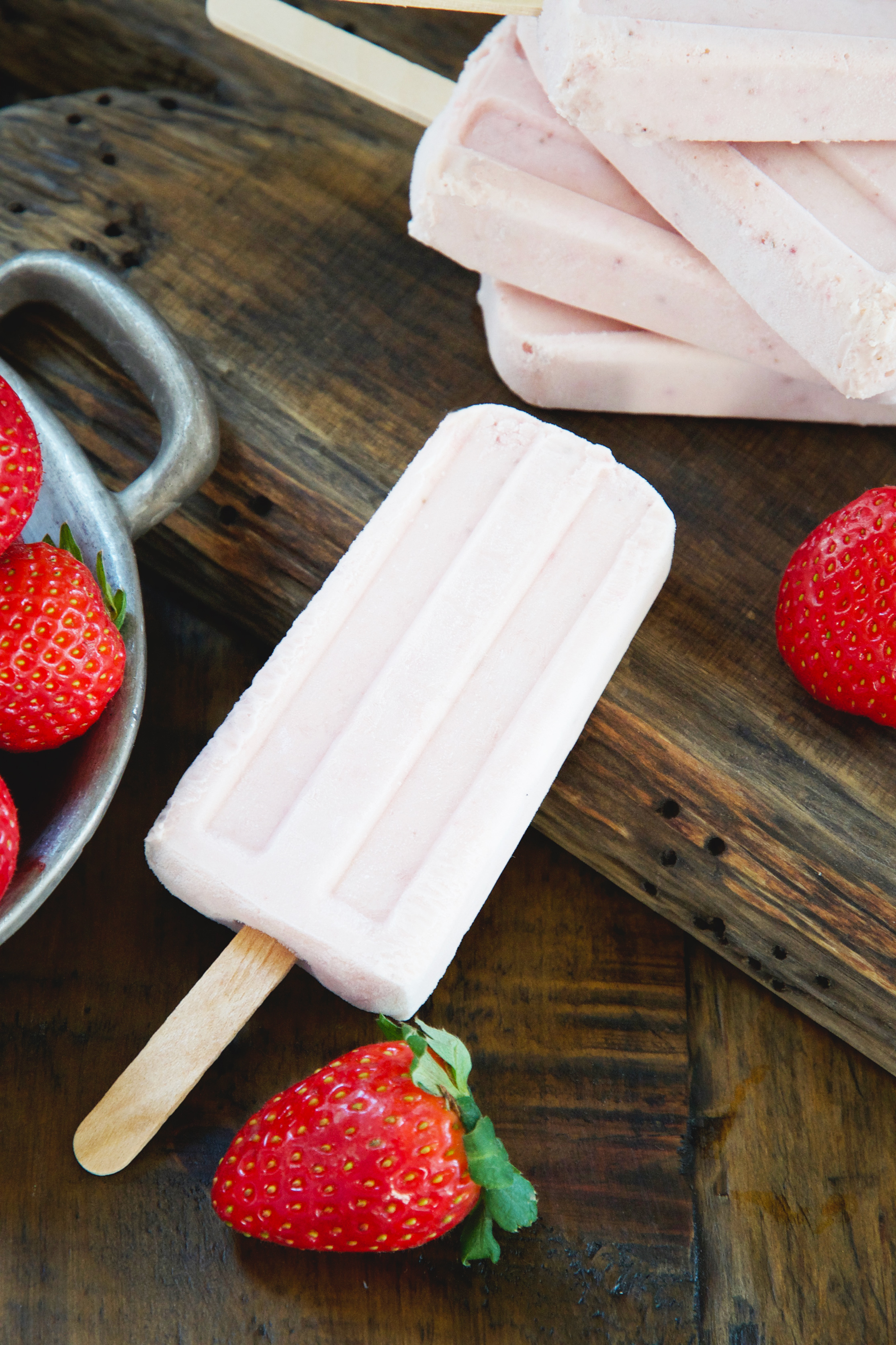 Low-Carb Strawberry Cream Popsicles One on cutting board with a stack behind.