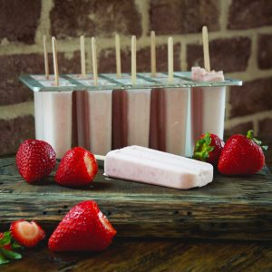 Low-Carb Strawberry Cream Popsicles-One out of the mold with others still in the mold.