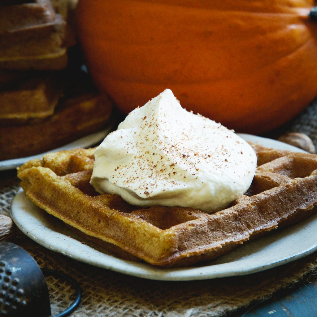 Pumpkin Low-Carb Almond Flour Waffle Recipe -whipped cream and nutmeg on top.