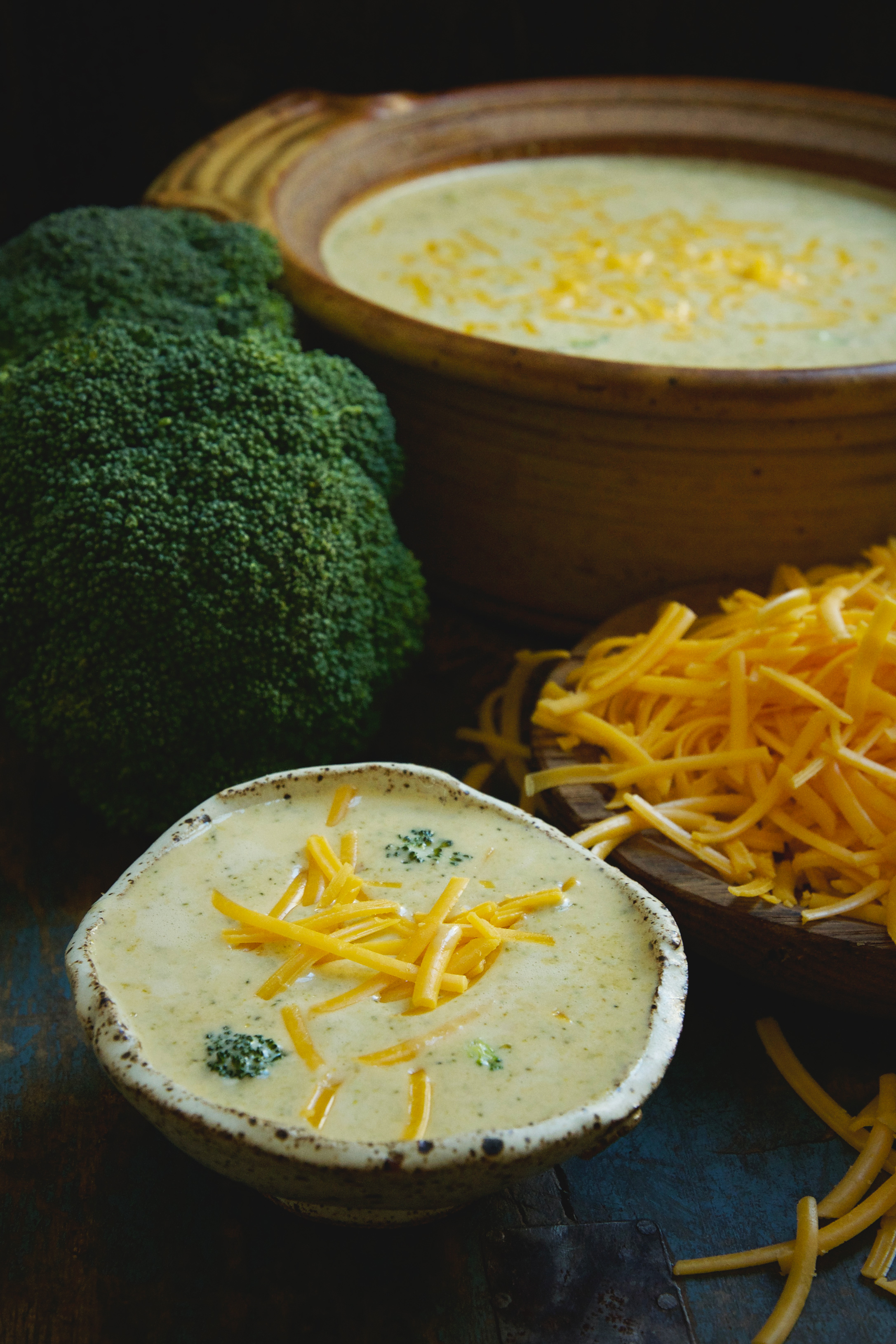 Low-Carb Broccoli Cheddar Soup Recipe-showing a serving and the rest of the soup in a pot.