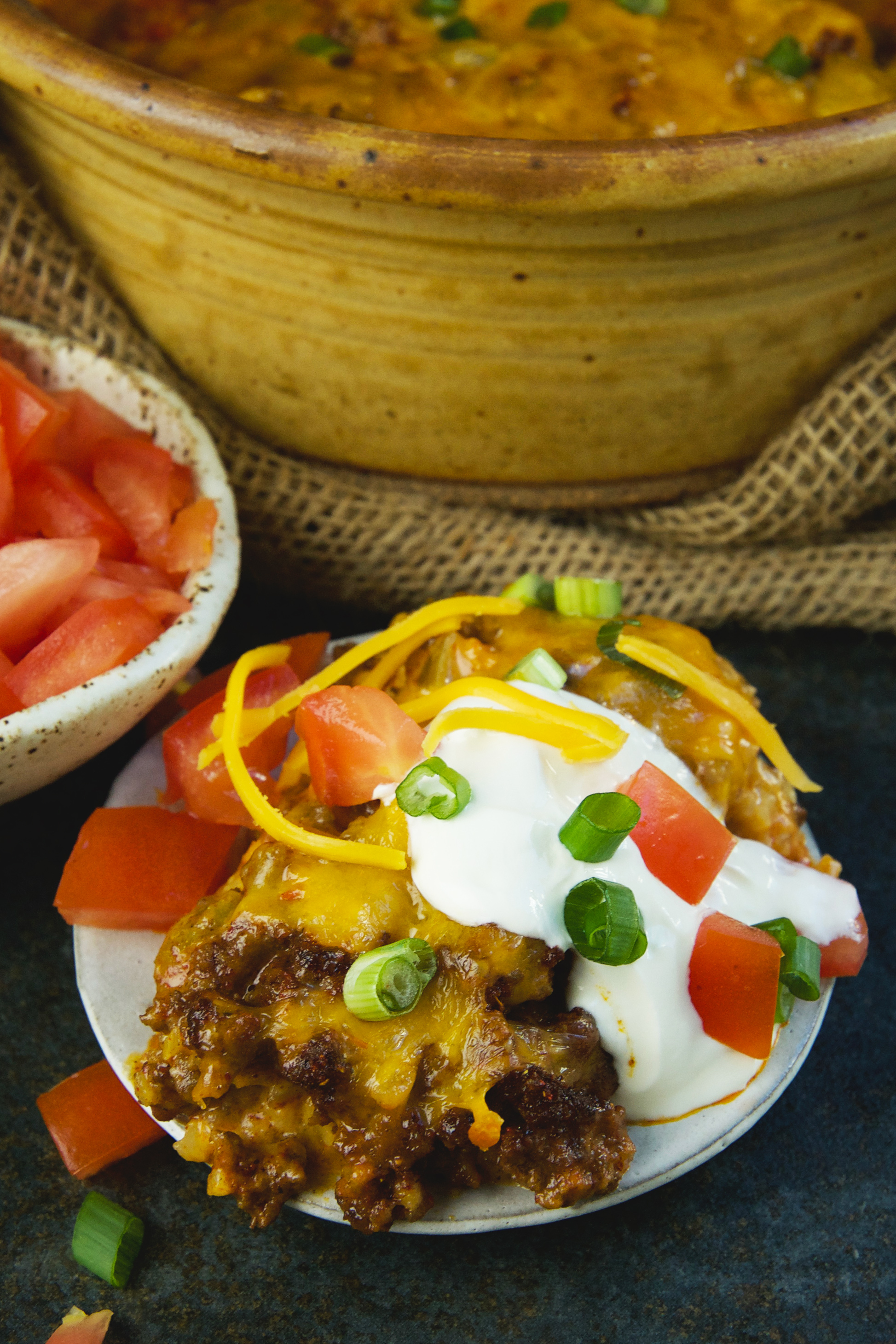 Low-Carb Mexican Taco Casserole-garnished with cream cheese, tomatoes and green onion