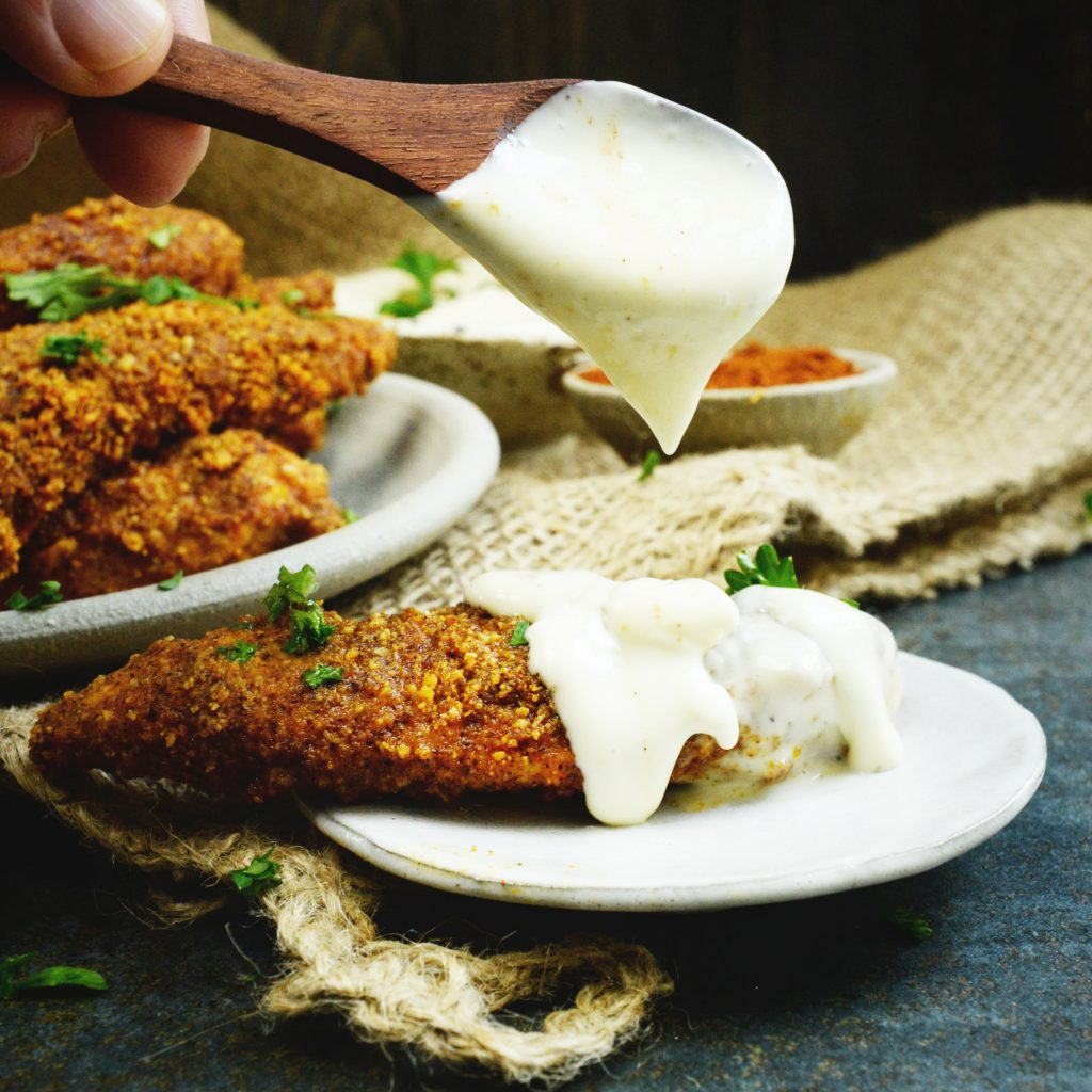Low-Carb Buffalo Chicken Tenders-Spooning blue cheese dressing over.