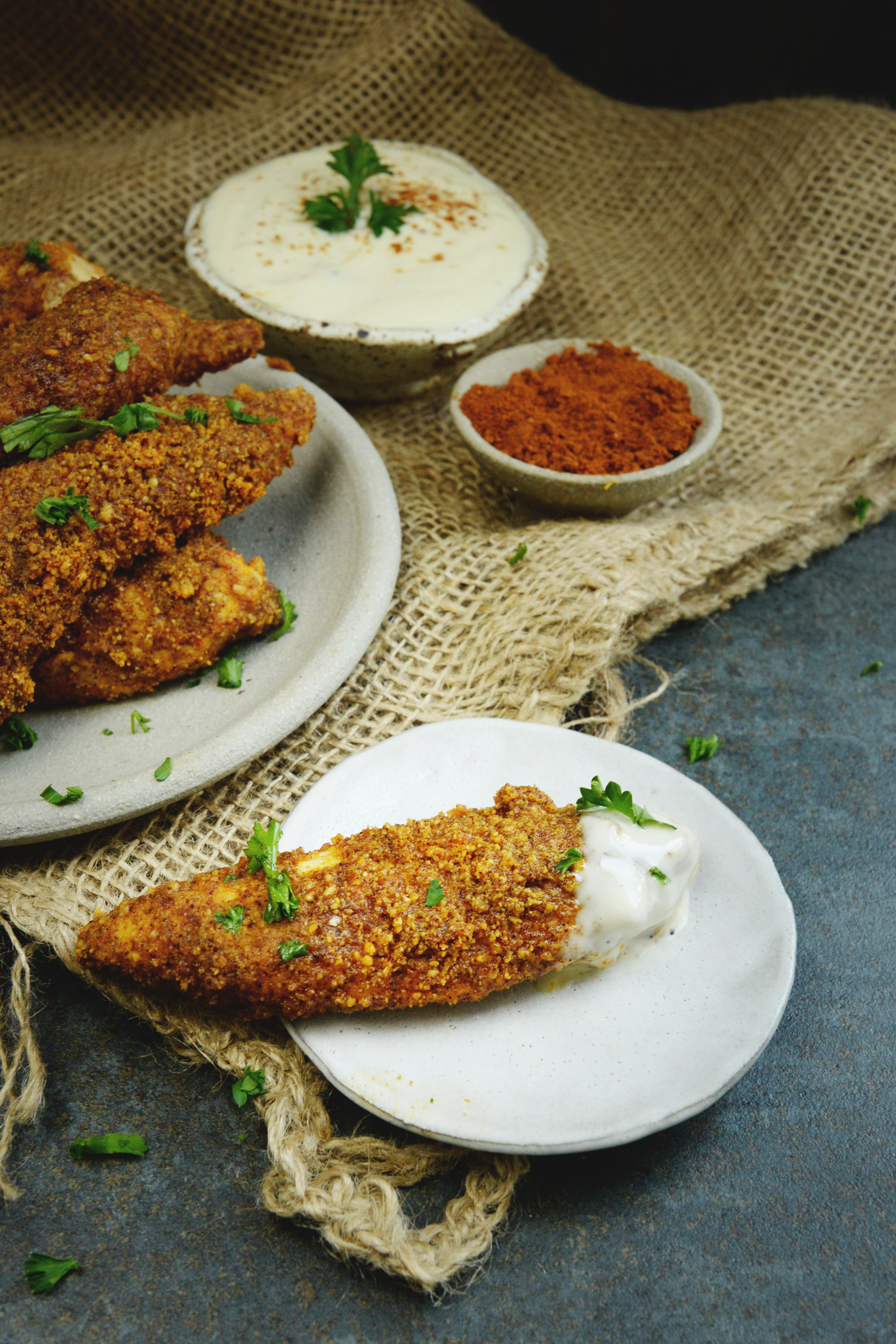 Low-Carb Buffalo Chicken Tenders-one shown dipped in dressing.