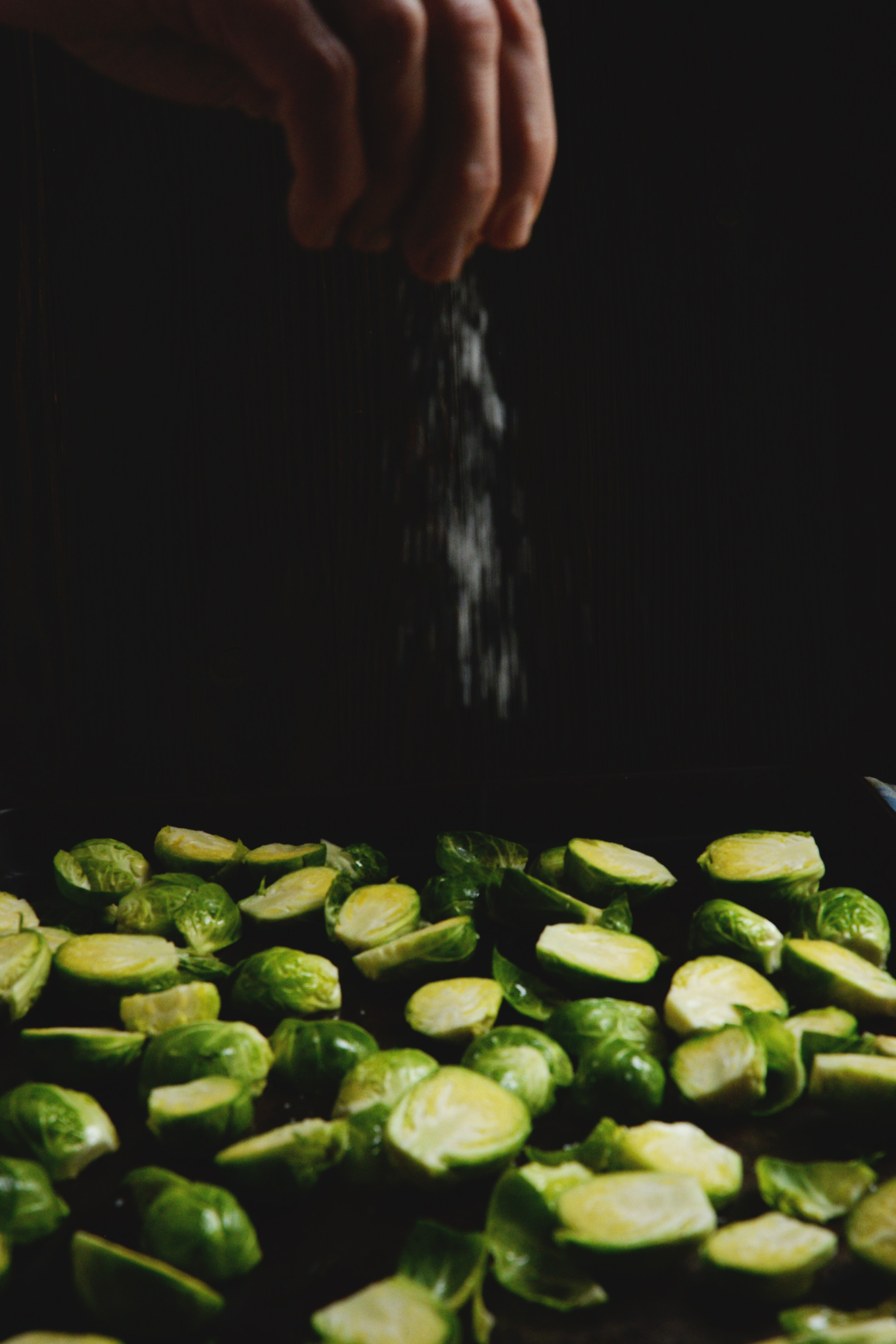 Easy Roasted Brussels Sprouts-sprinkling with salt.
