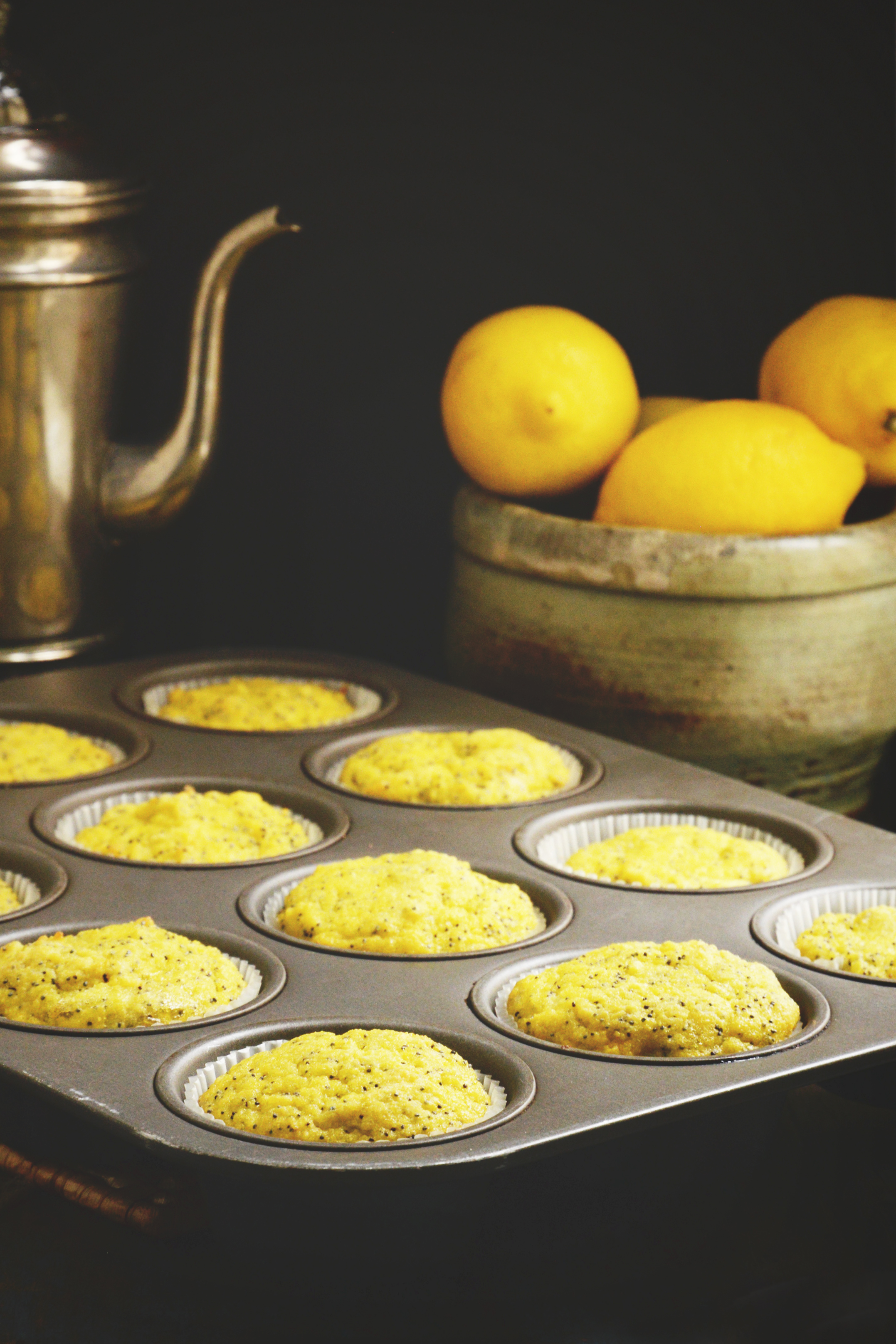 Lemon-Poppy-Seed-Muffins-in the tin with lemons and coffee pot behind.