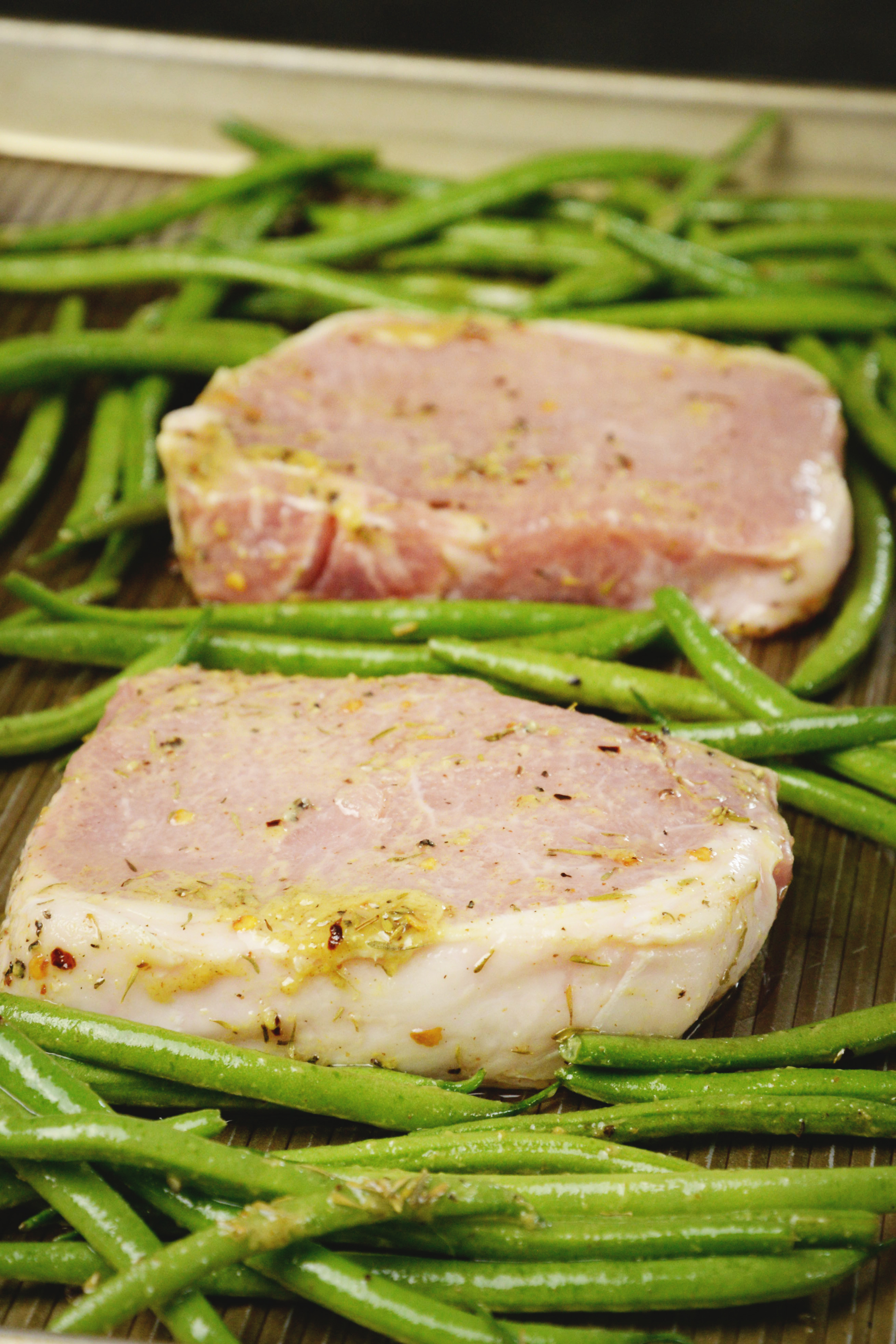 heet Pan Pork Chops with Green Beans-Close up of chops and beans ready for the oven.