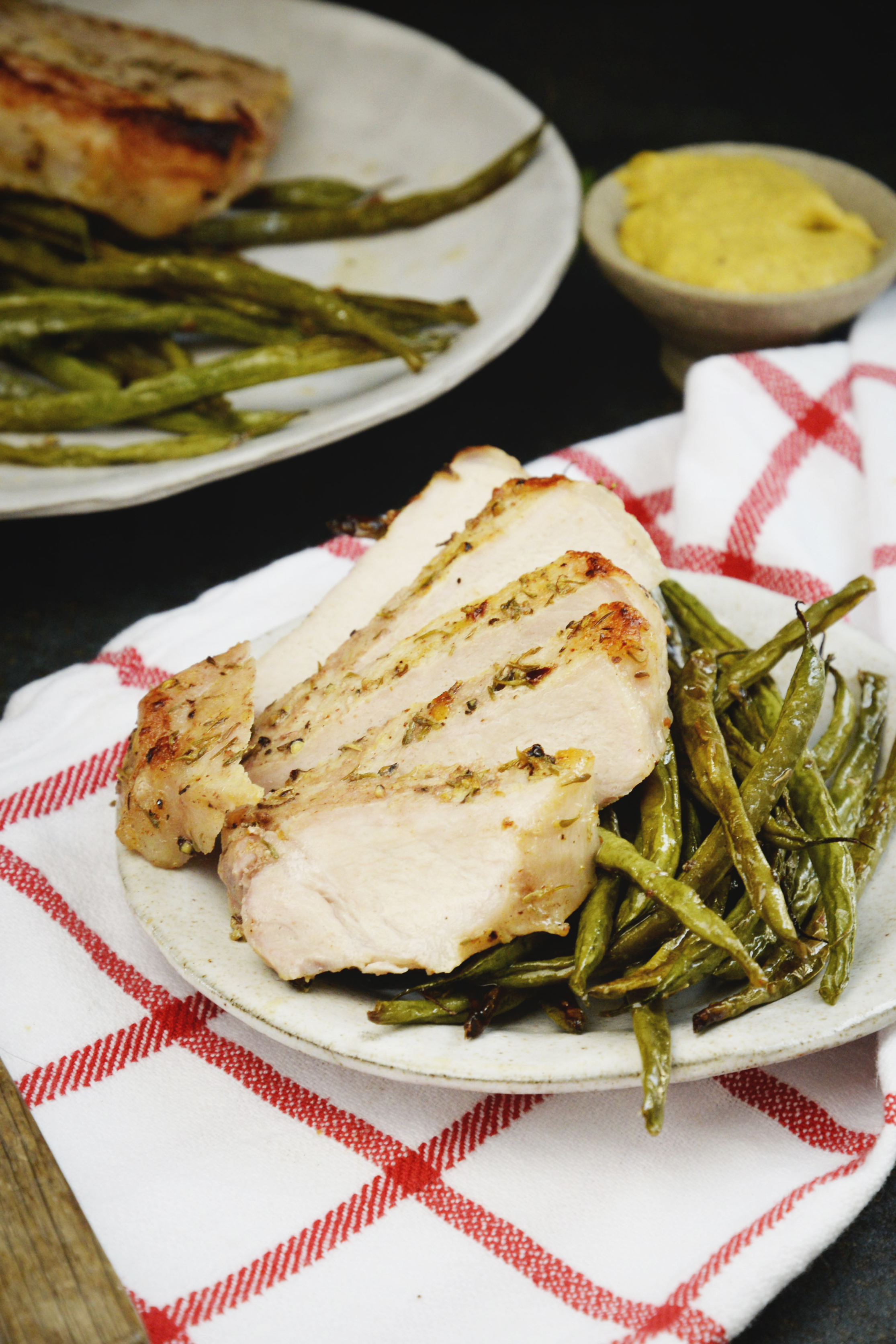 heet Pan Pork Chops with Green Beans-pork chop sliced and on a plate.