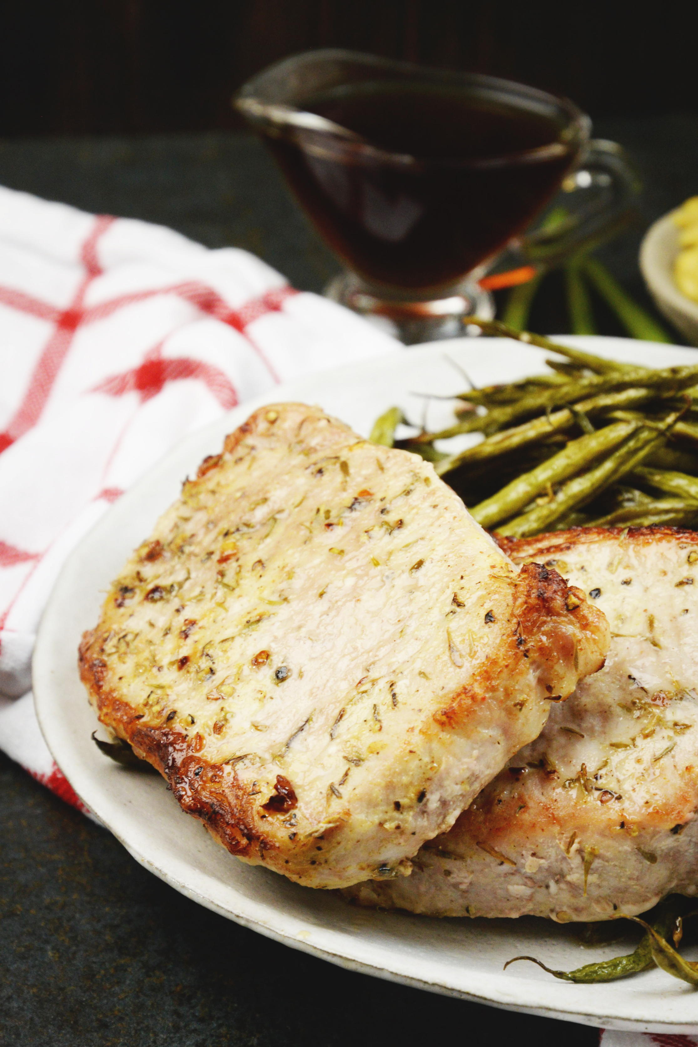heet Pan Pork Chops with Green Beans-serving the chops and beans on a plate.
