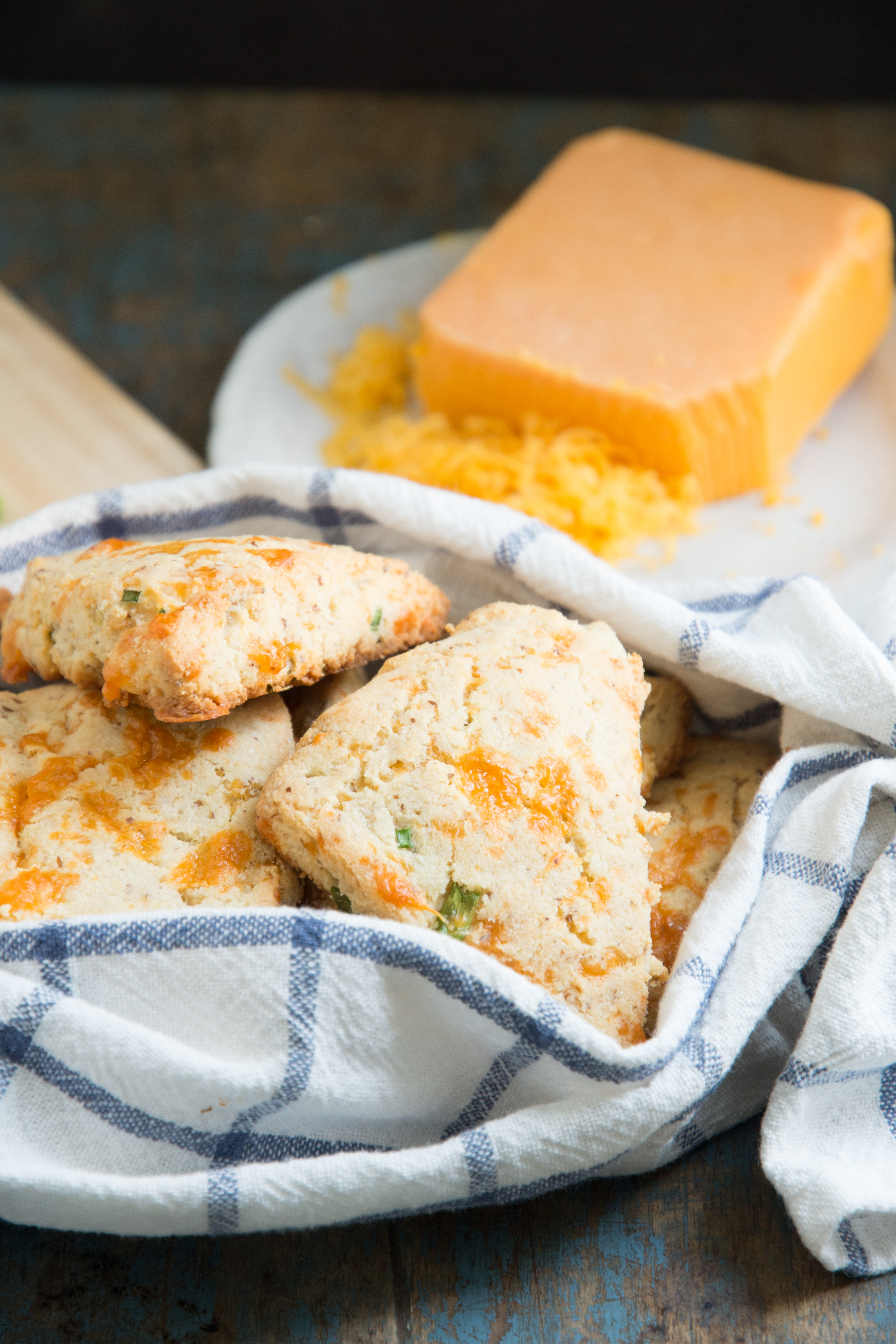Low-Carb Cheddar Biscuits -In a cozy with cheesecake behind.