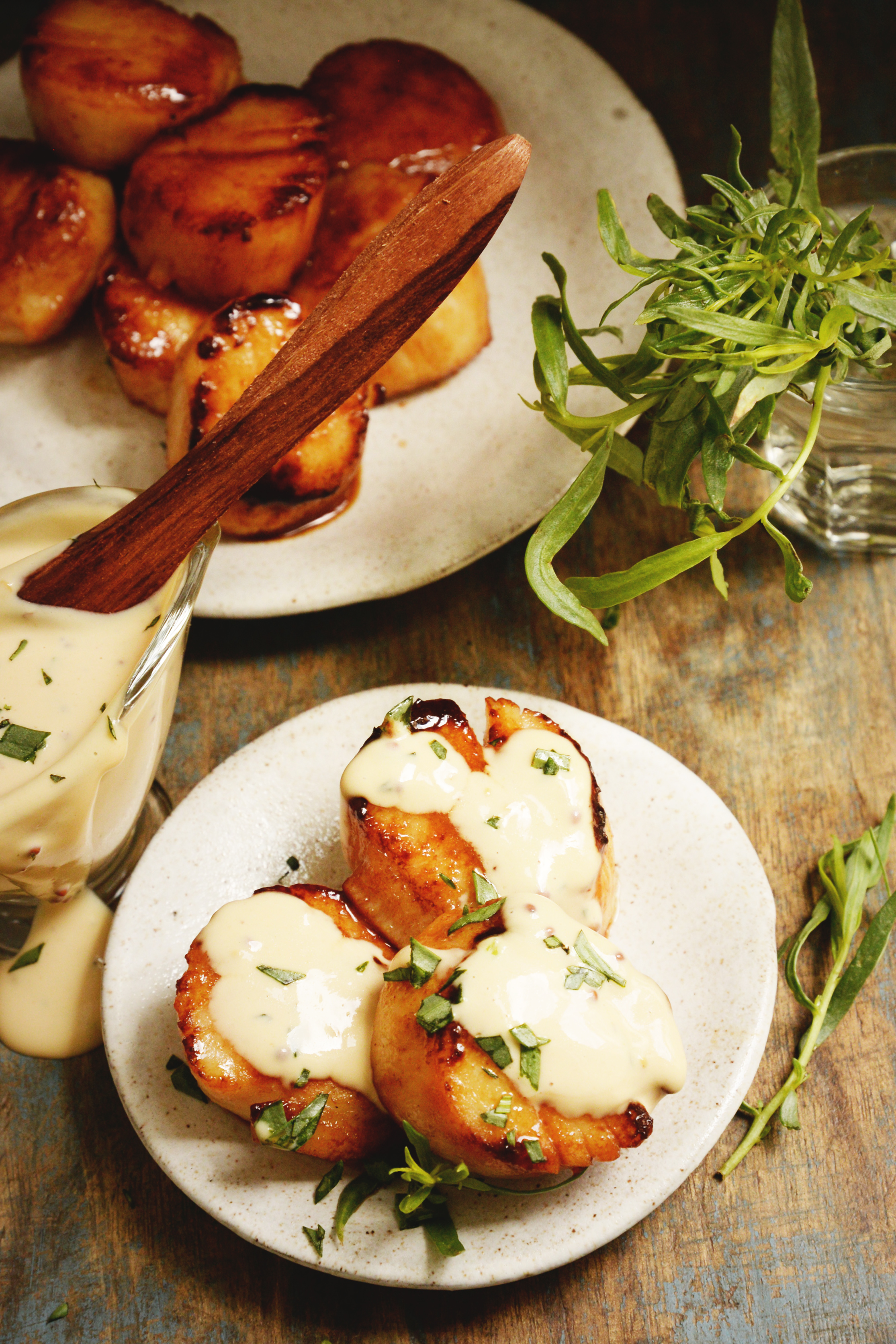 Pan Seared Scallops with Tarragon Cream Sauce-overhead shot with some on a plate with sauce on it.