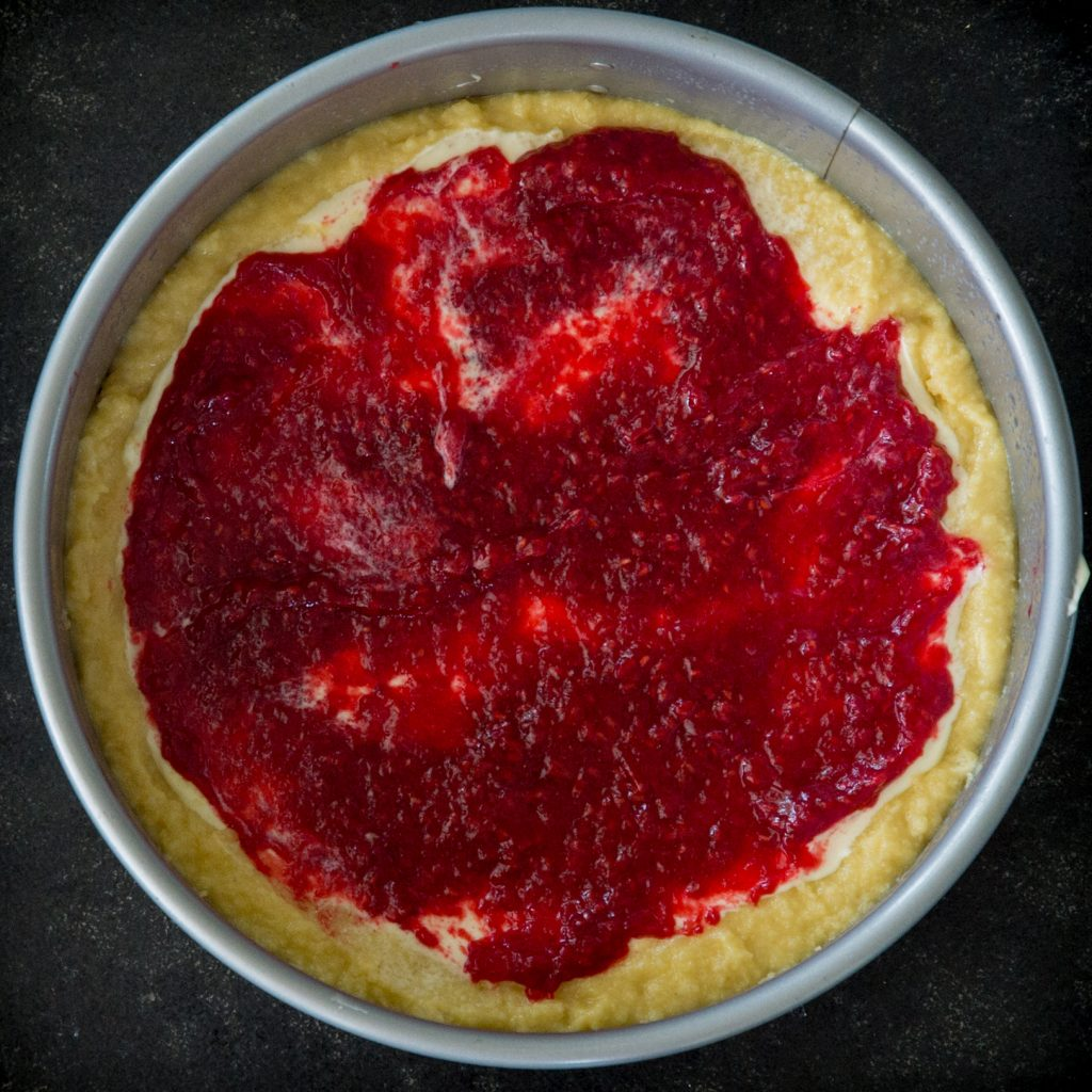 Keto Raspberry Cream Cheese Coffee Cake-adding the raspberry sauce.