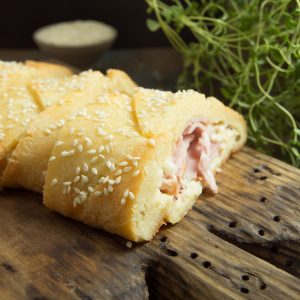 Side view of Low-Carb Ham and Cheese Sandwich Braid on a wooden board.