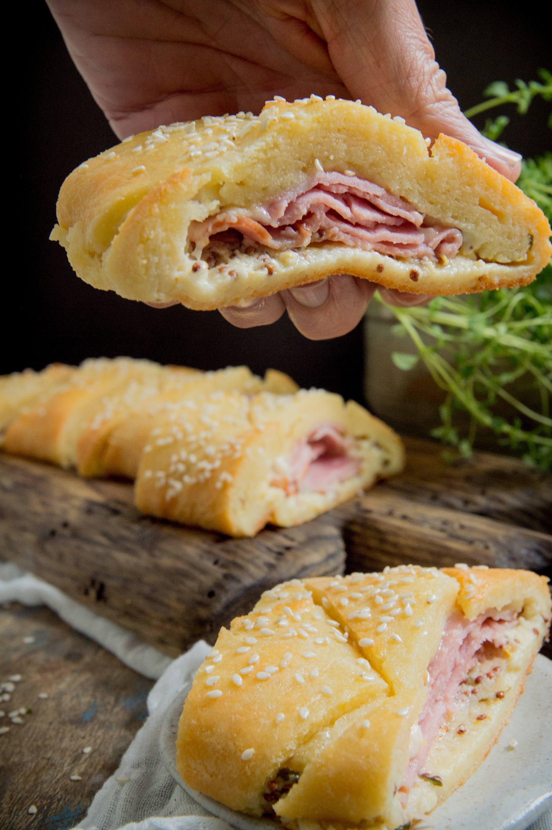 Low-Carb Ham and Cheese Sandwich Braid-holding a slice.