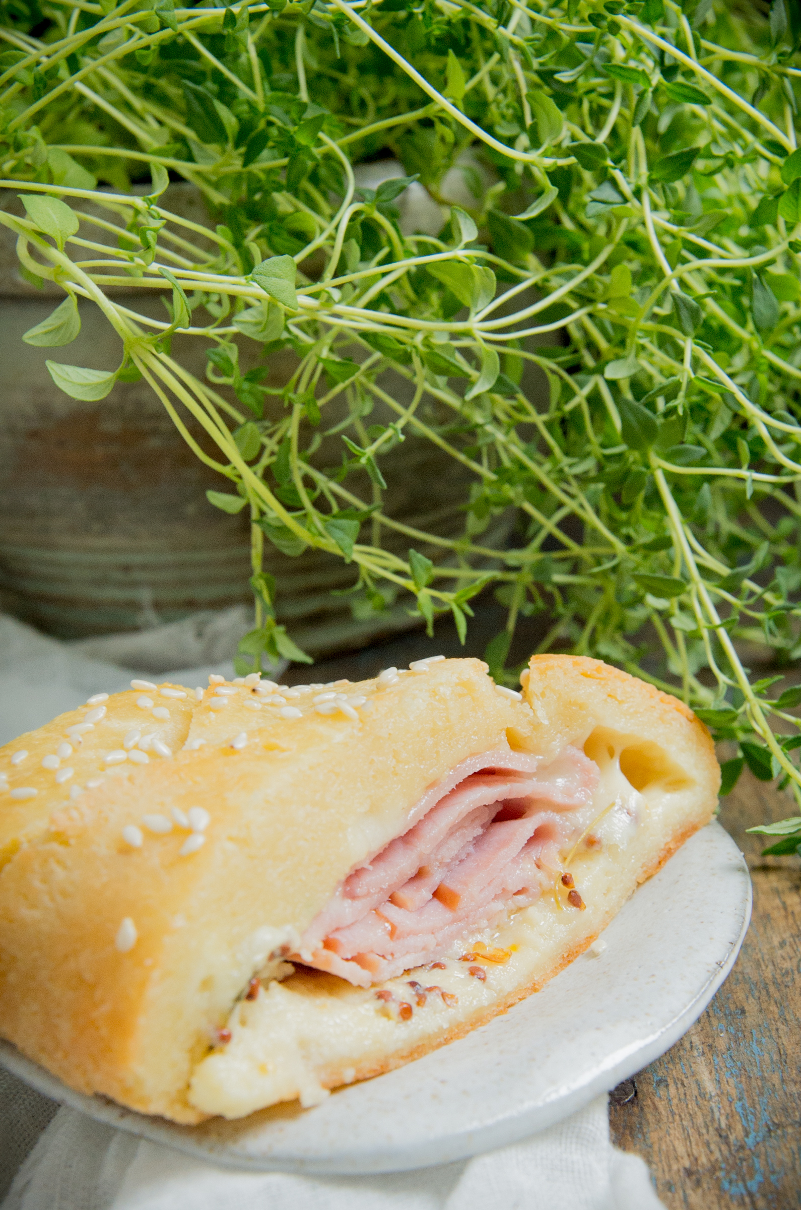 Low-Carb Ham and Cheese Sandwich Braid-a slice with thyme in the background.
