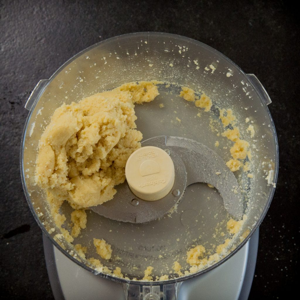 Adding the butter to the crust in a food processor.
