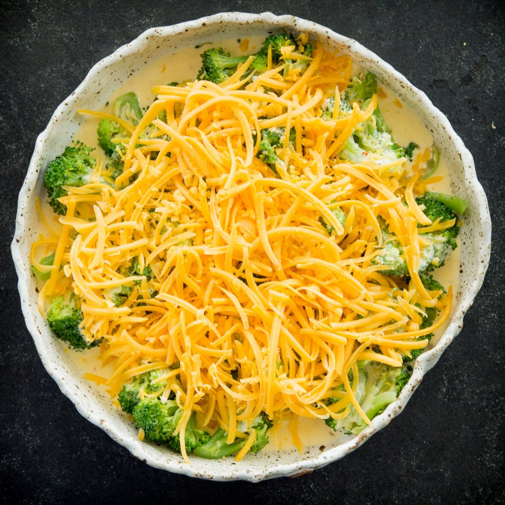 Low-Carb Keto Broccoli Cheese Casserole-Topping it with cheese.