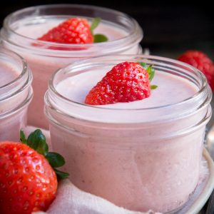 Overhead shot of Low-Carb Strawberry Mousse in jars with strawberries.