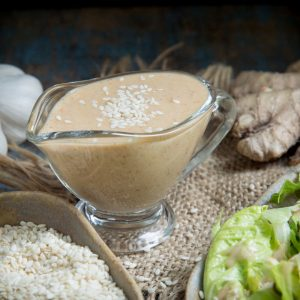 Low-carb sesame ginger salad dressing on a glass gravy boat.