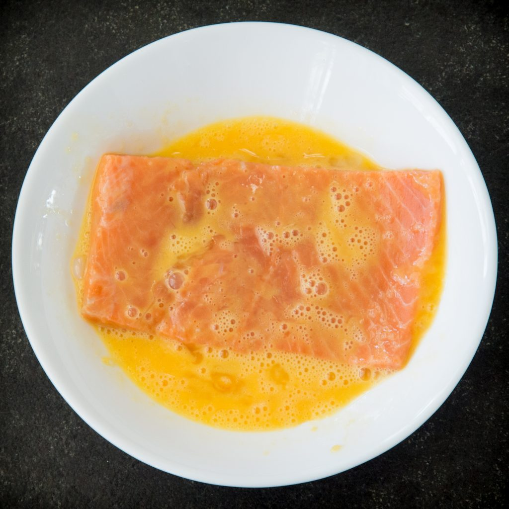 Dipping salmon in beaten egg.