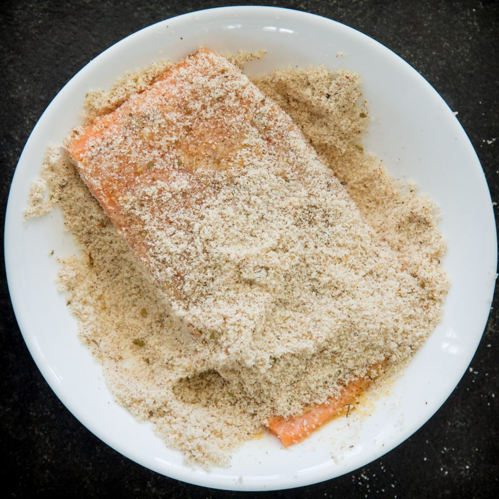Dredging raw salmon in breading.