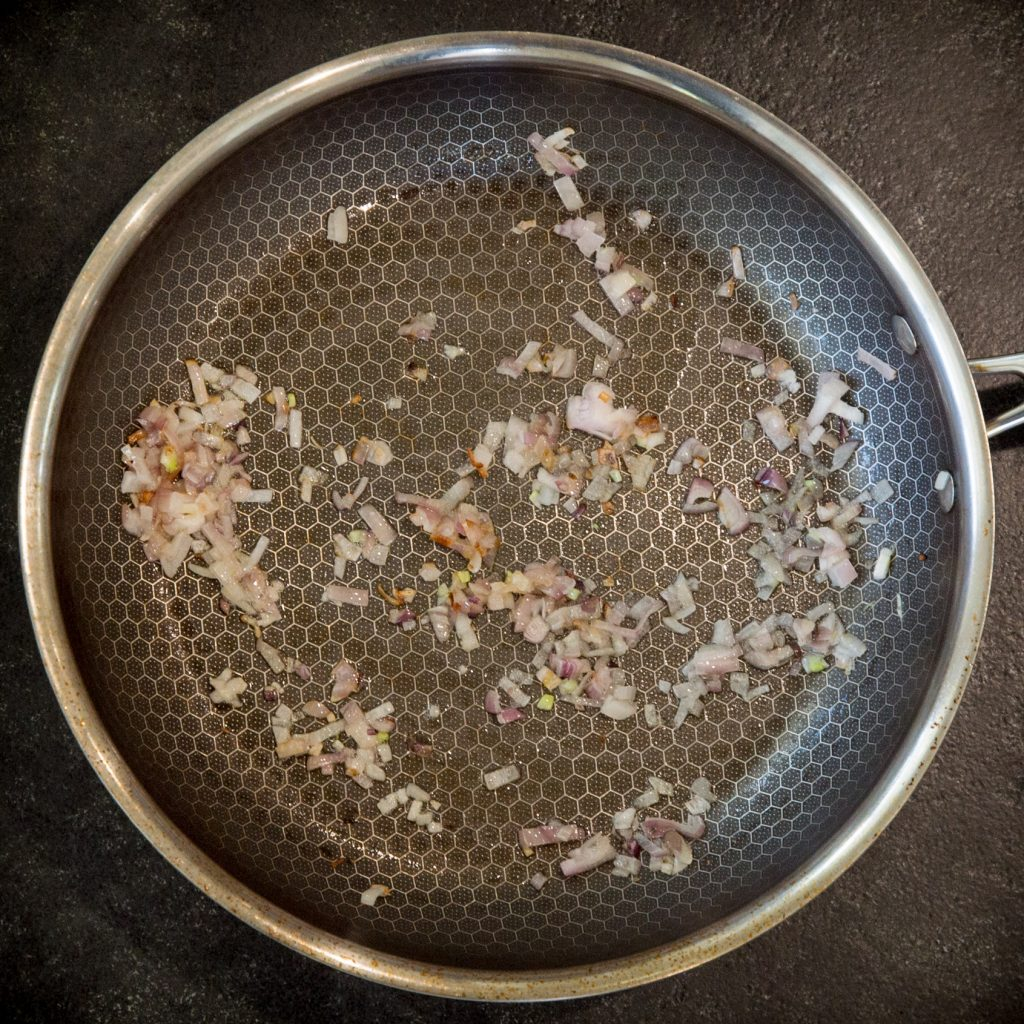 Cooking the shallots in a pan.