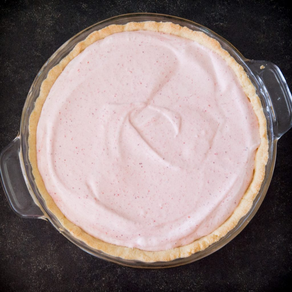 Overhead photo of pie with strawberry cream on it.