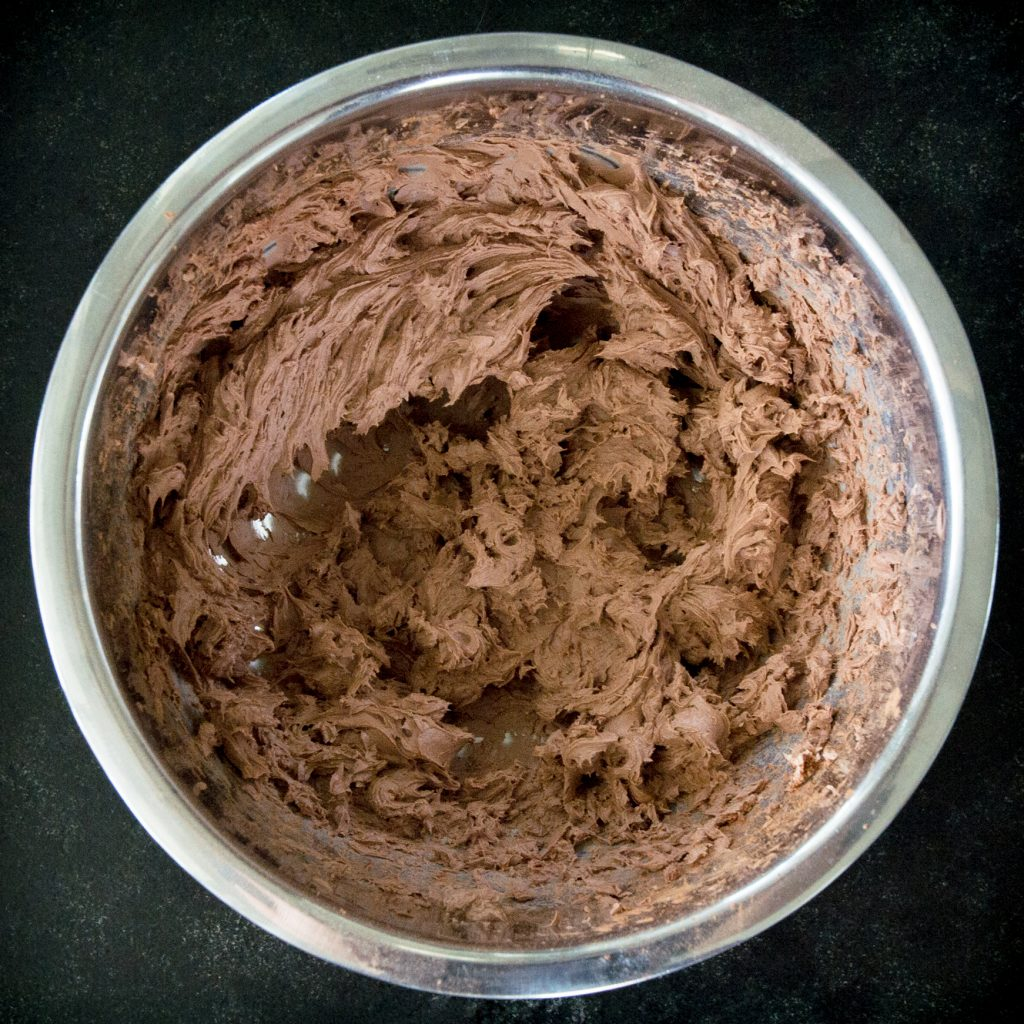 Overhead process photo of whipped cream cheese and cocoa powder.