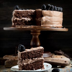 Slice of Chocolate Cake in front of cake on cake stand.
