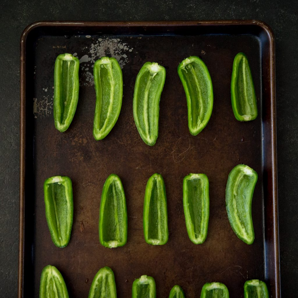 raw jalapeno pepper halves on a cookie sheet