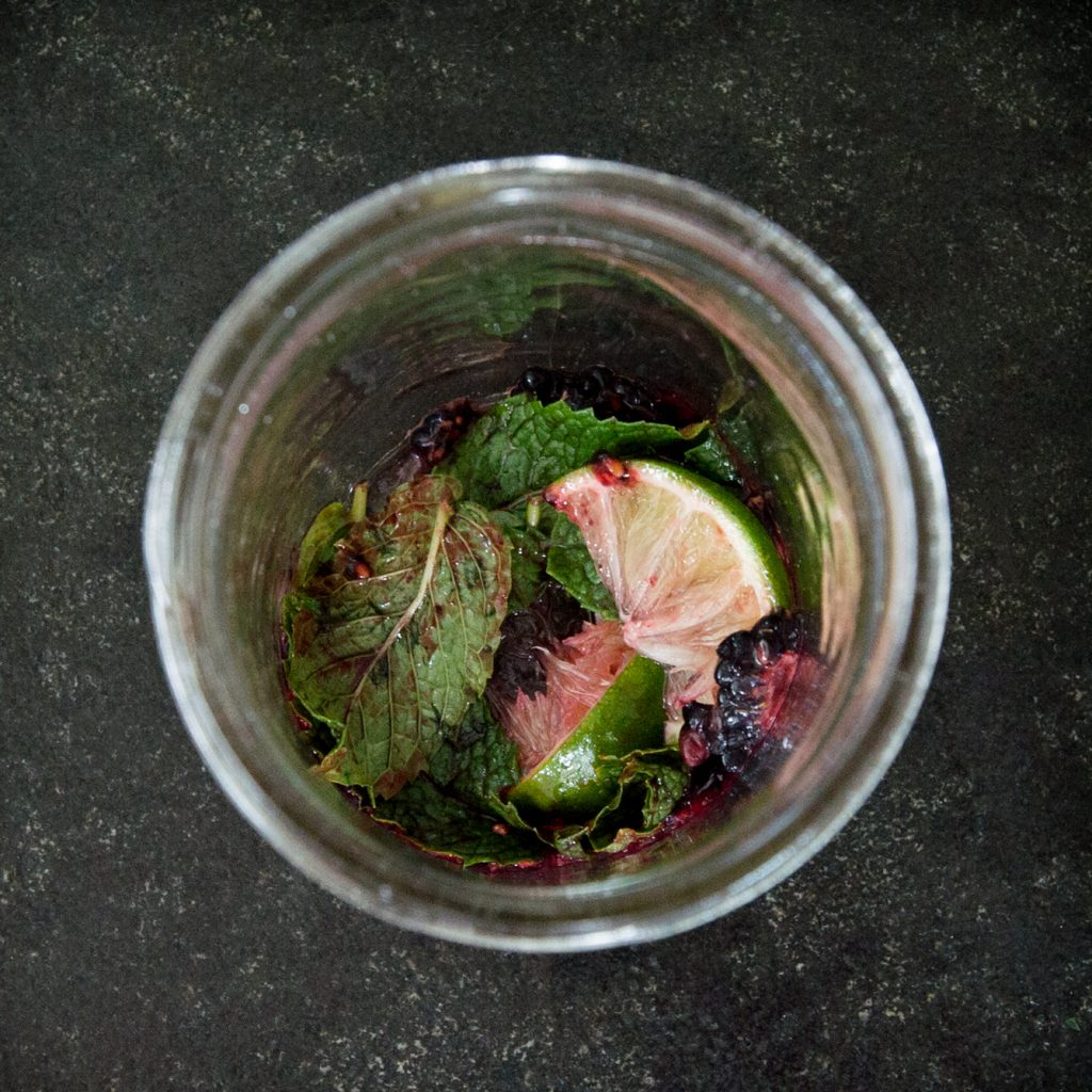 Overhead process photo of low-carb blackberry mojito ingredients in a glass.