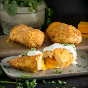 Taco crusted cheese stuffed chicken breast cut in half on a plate.