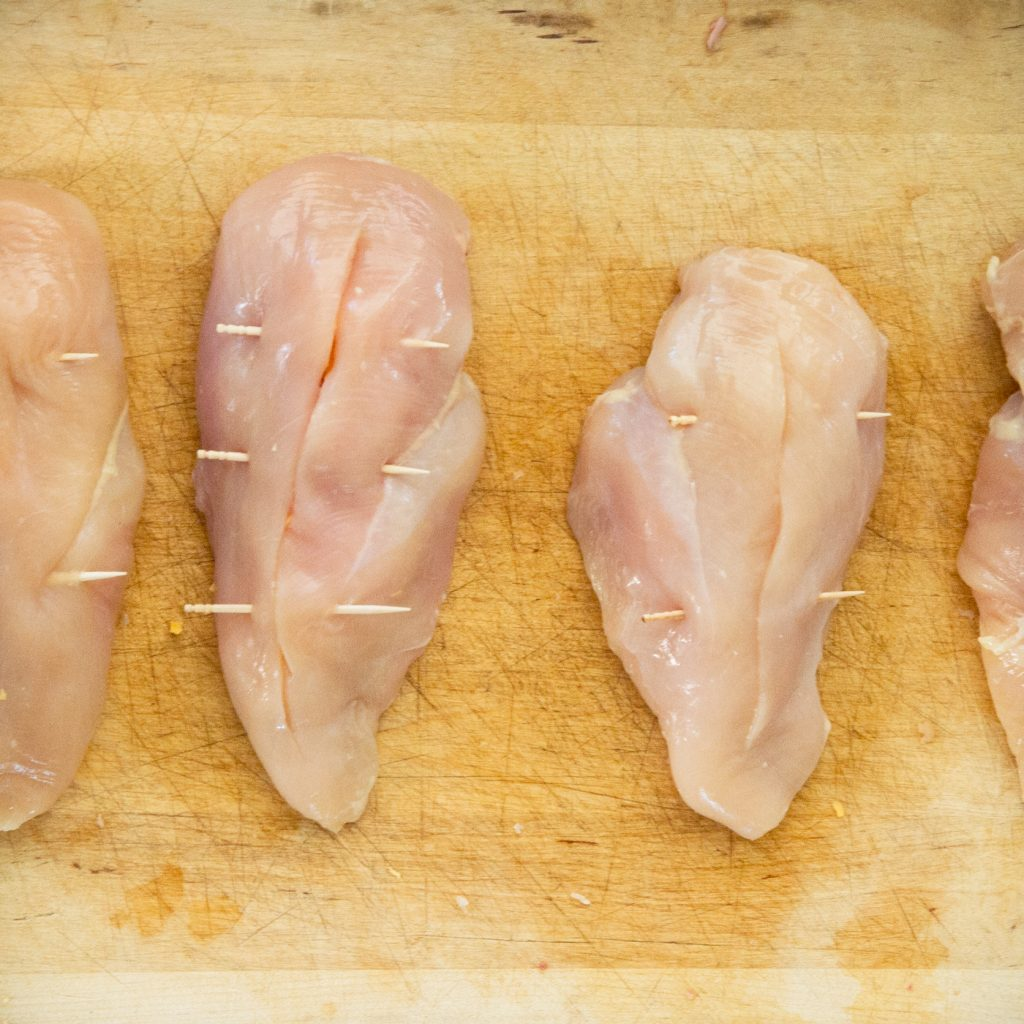 Process photo of raw chicken breasts secured with toothpicks.