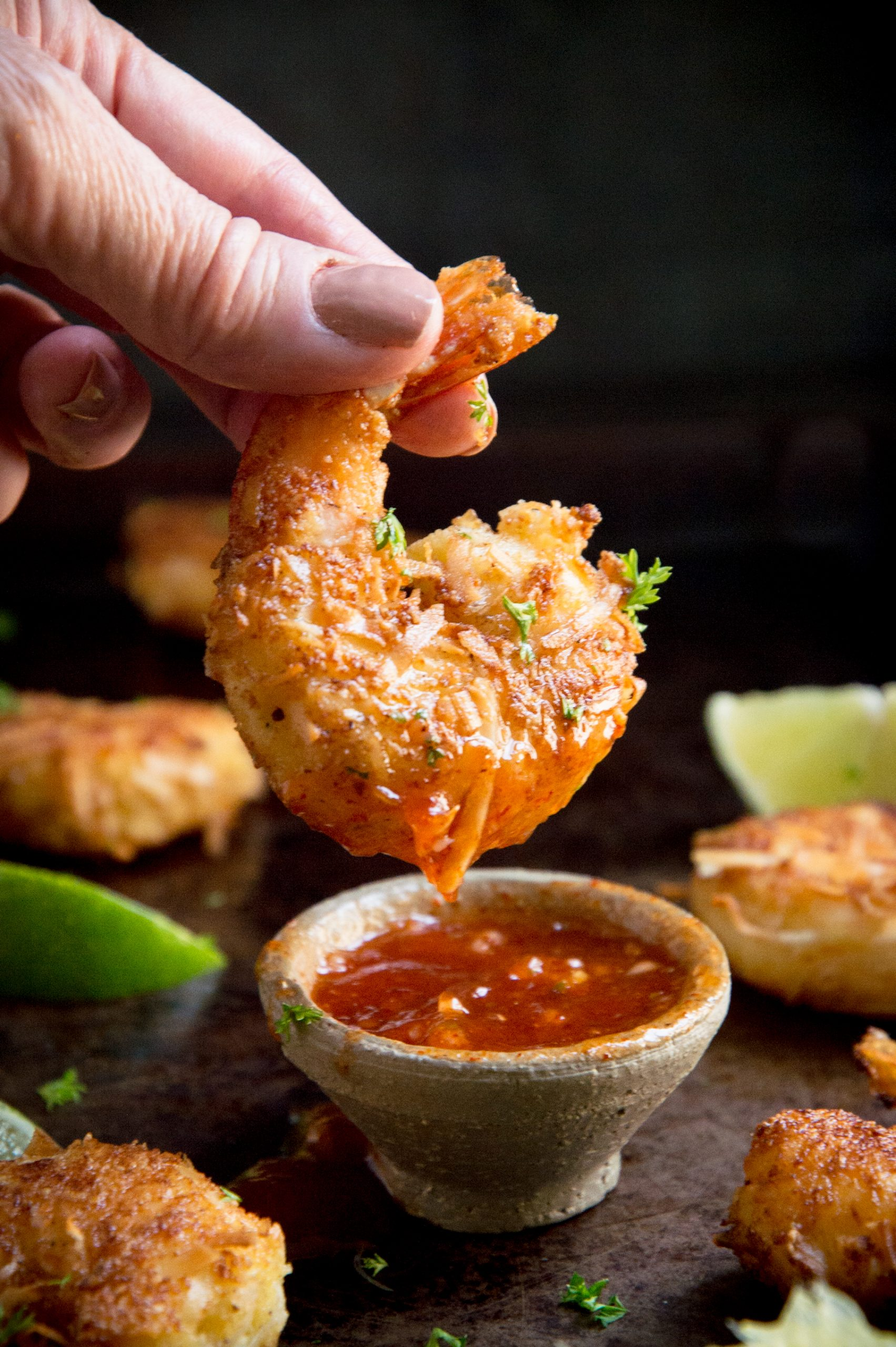 Close up of a gluten-free fried shrimp dipped in sauce